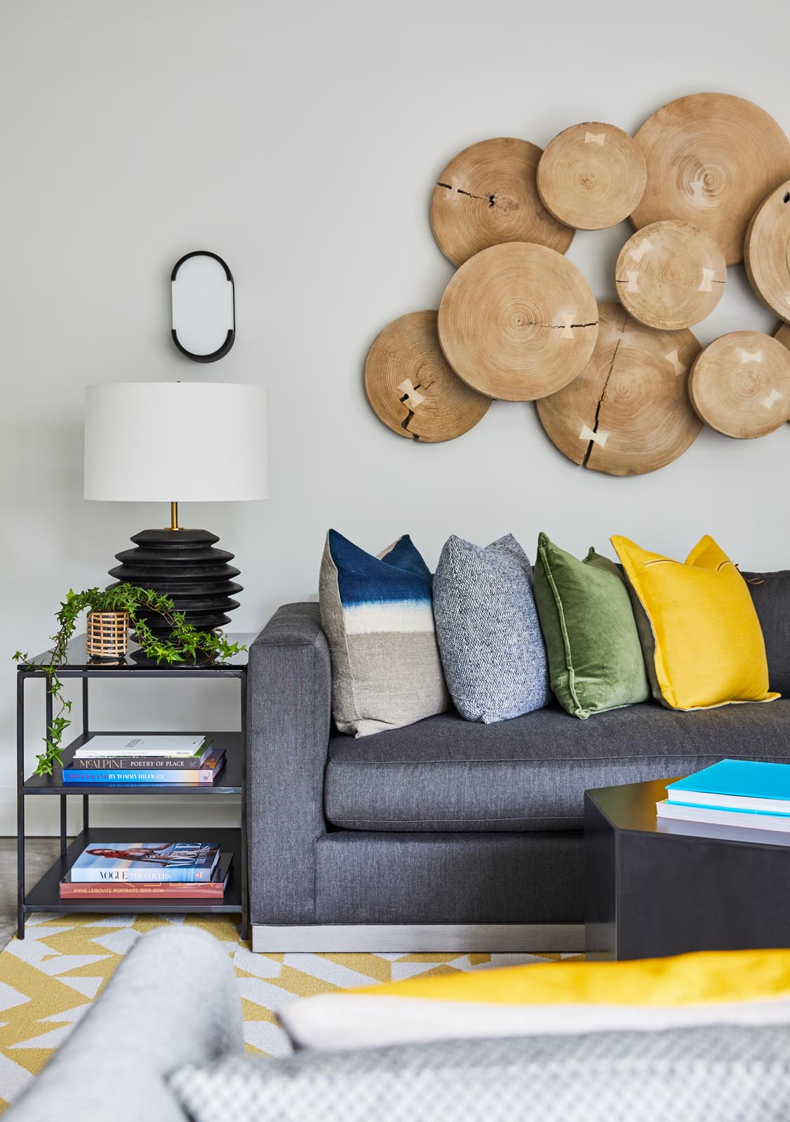 A modern media room with yellow accents, and a large wood art piece on the wall.