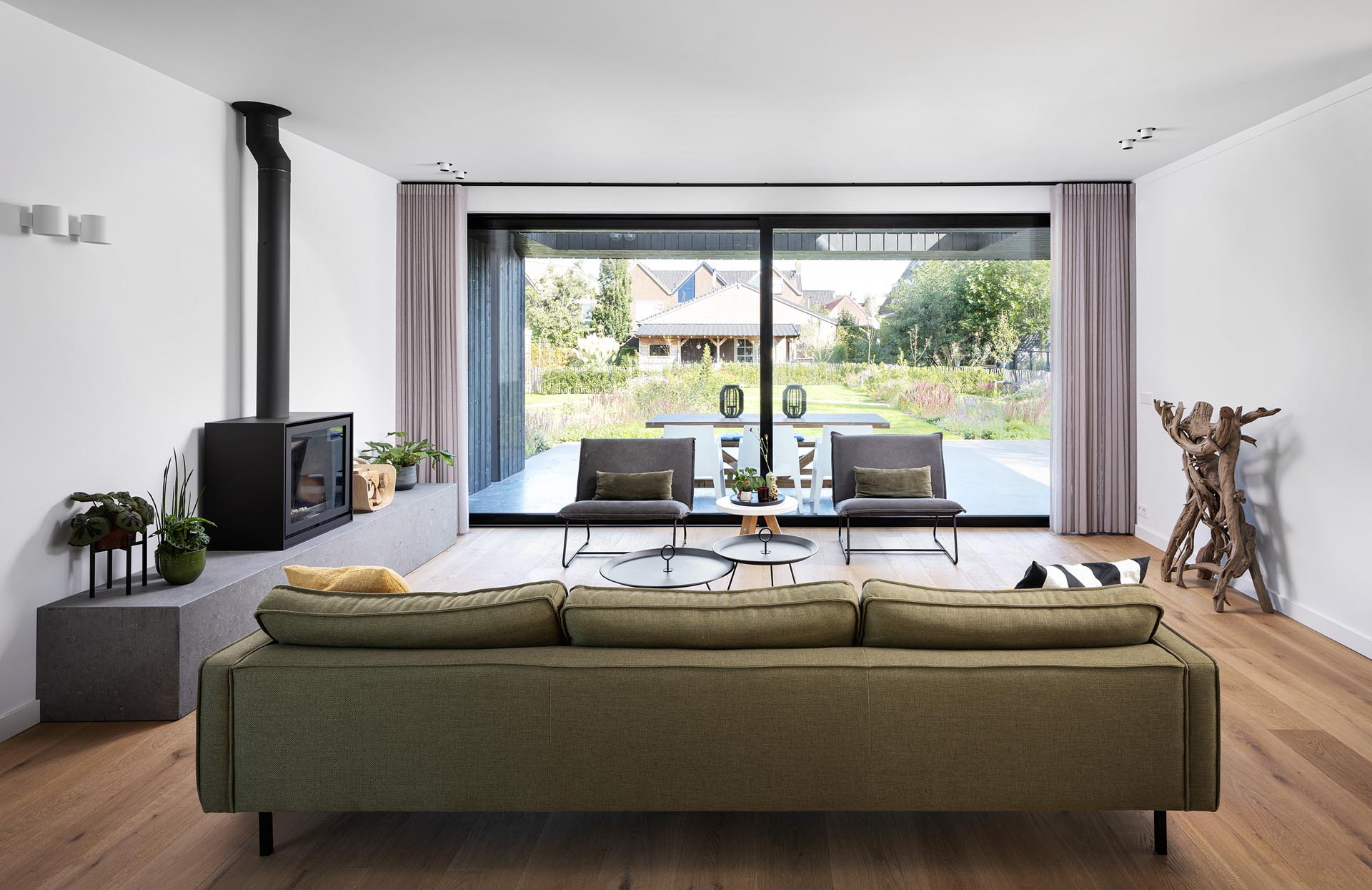 Inside a modern home, the furnishings have been kept minimal, while large sliding doors open the living room to an outdoor patio that's been set up for alfresco dining.