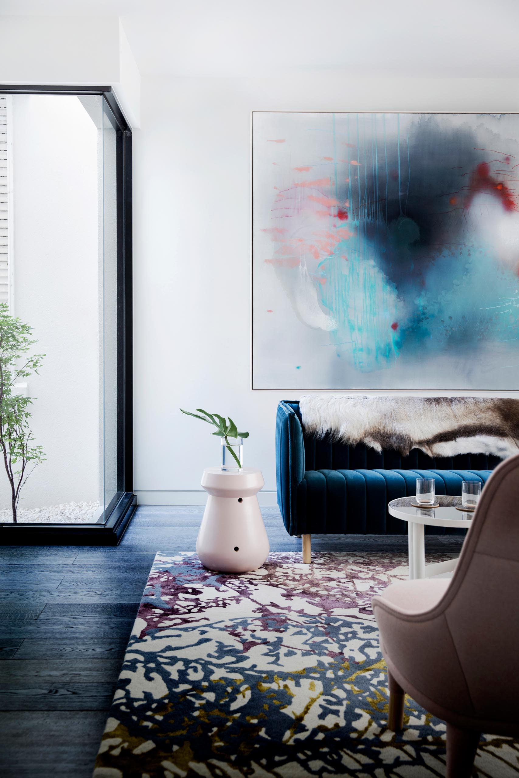 A modern living room with blue and blush pink furniture accents.
