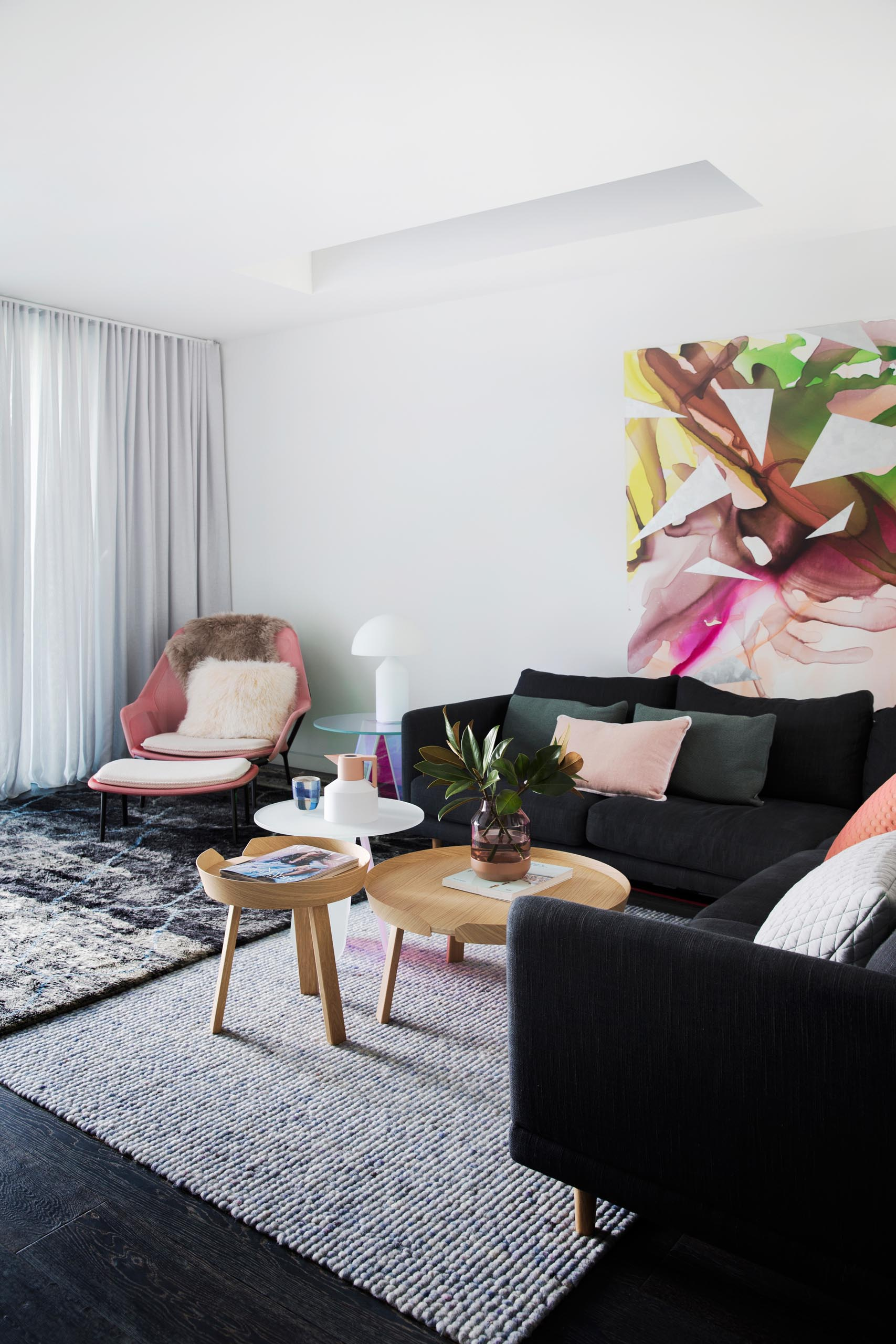 A modern living room with blush pink decorative accents.