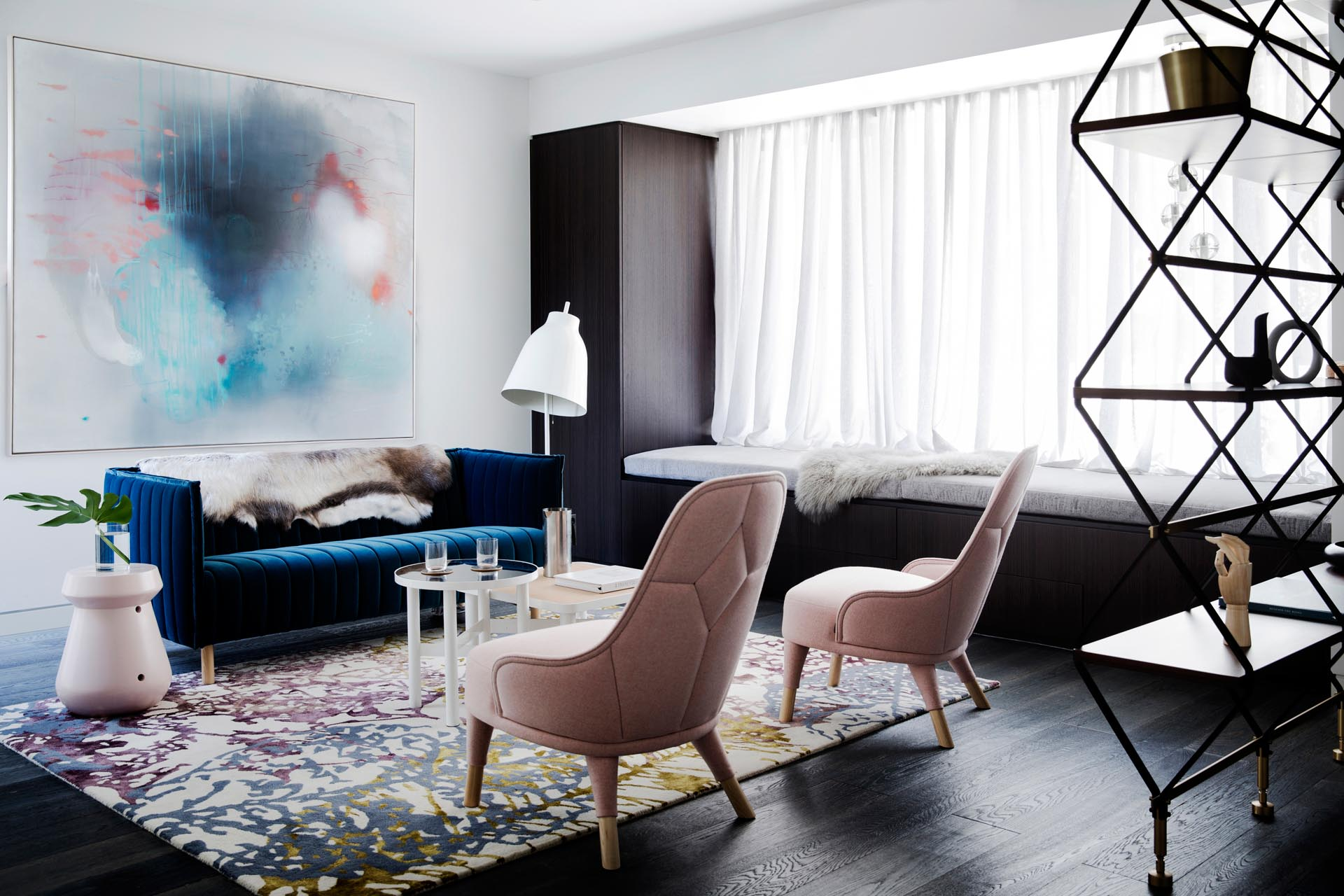 A modern living room with a built-in window bench, and blue and blush pink furniture accents.