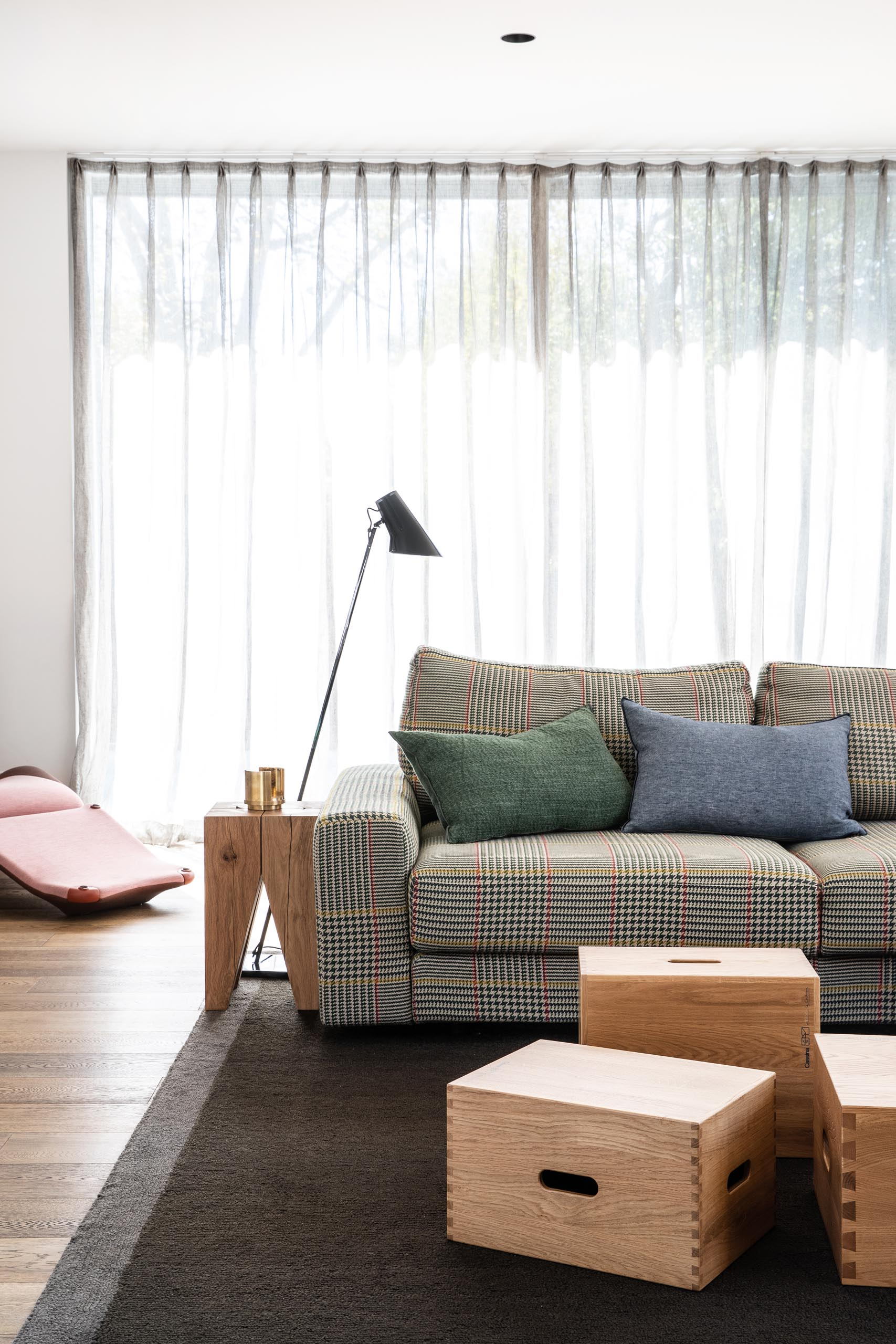 This modern living room is defined by a large dark colored rug, while wood boxes have been used to create a coffee table.