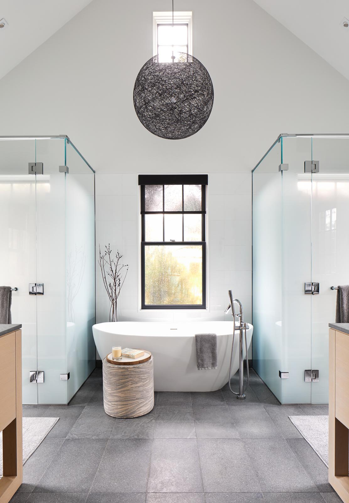 In this modern master bathroom, there's a freestanding bathtub that rests in front of the window, while frosted glass hides the showers.