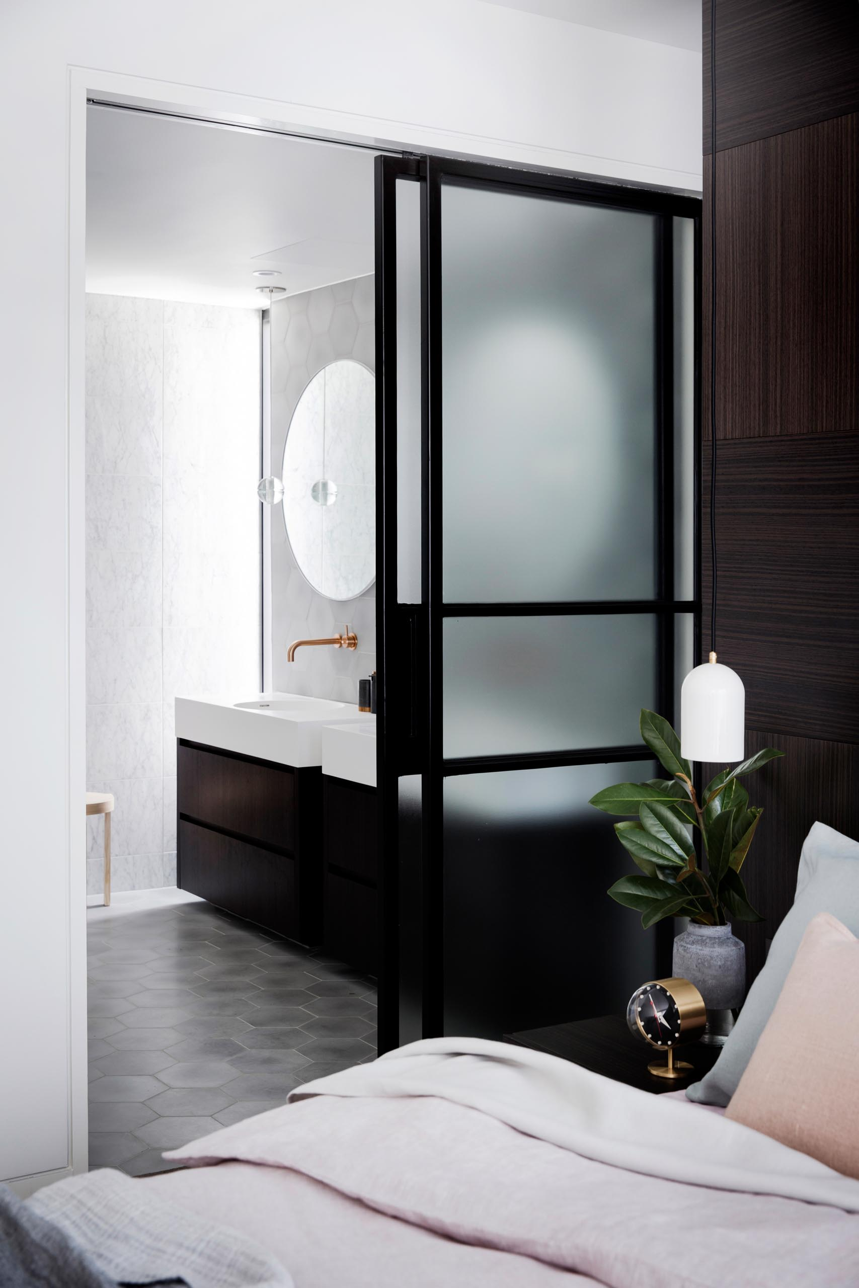 A black framed frosted glass door that slides open to reveal a modern en-suite bathroom.