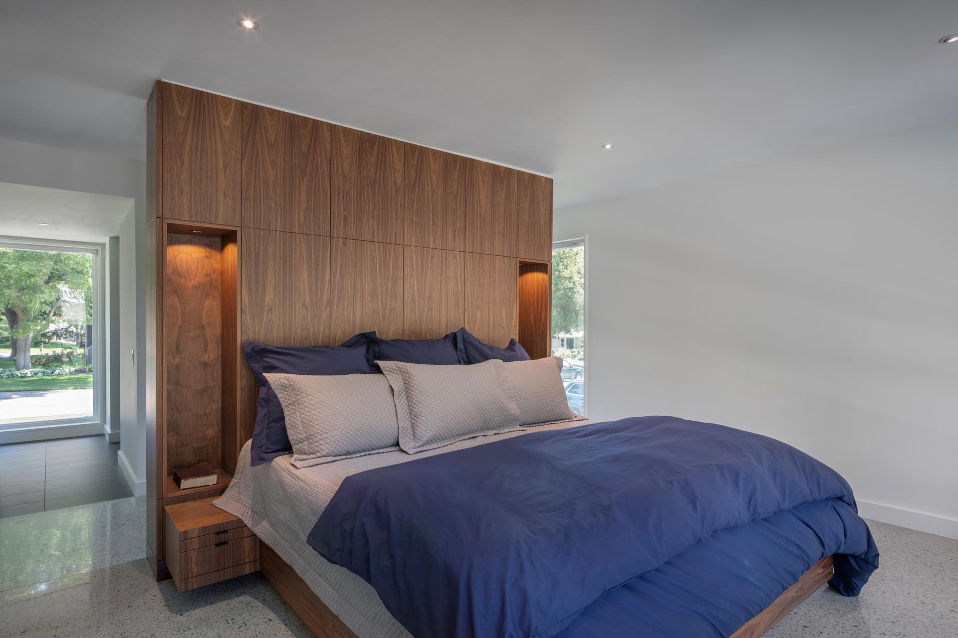 A modern bedroom with a a wood accent wall that has voids, allowing for built-in bedside lamps.