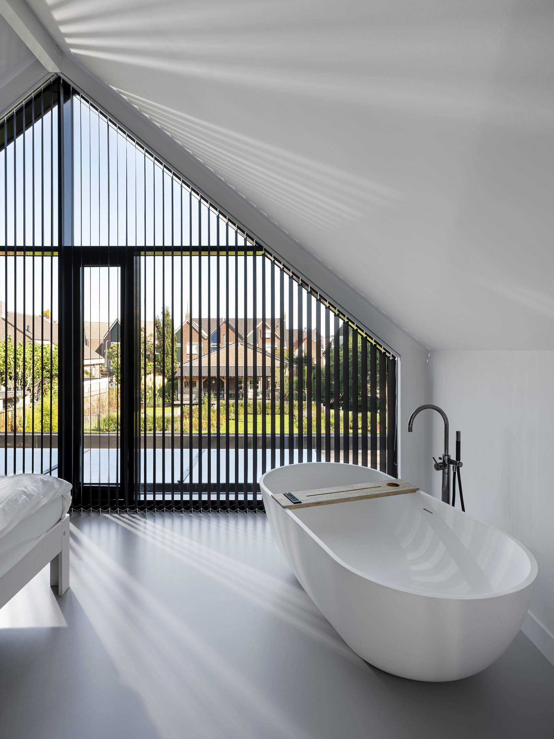 This modern master bedroom has windows that match the roof line and a freestanding bathtub.