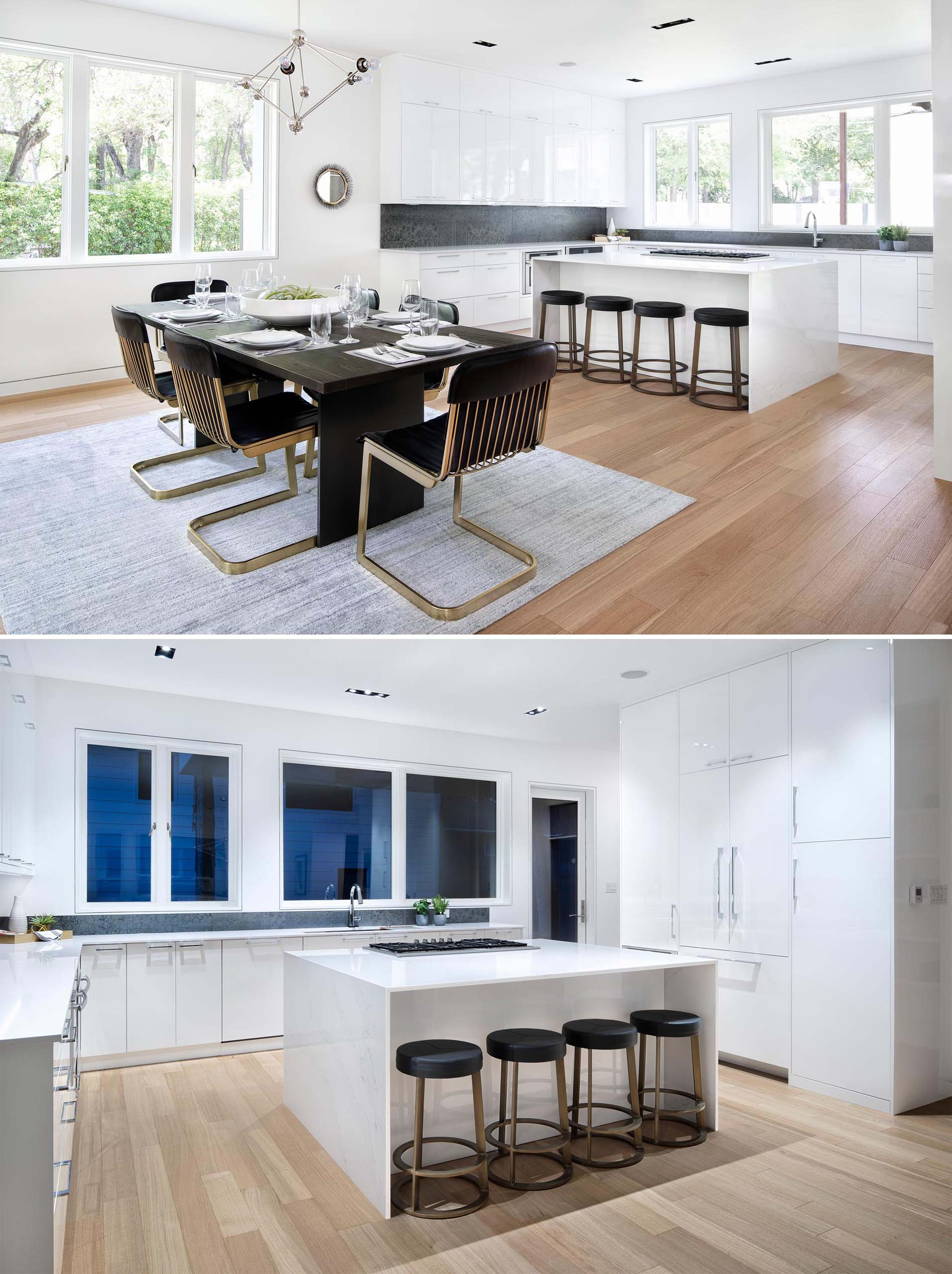 The dining area in this modern home is defined due to the placement of the rug on the wood floor, while the kitchen has modern white cabinets, a contrasting backsplash, and a central island with room for seating.
