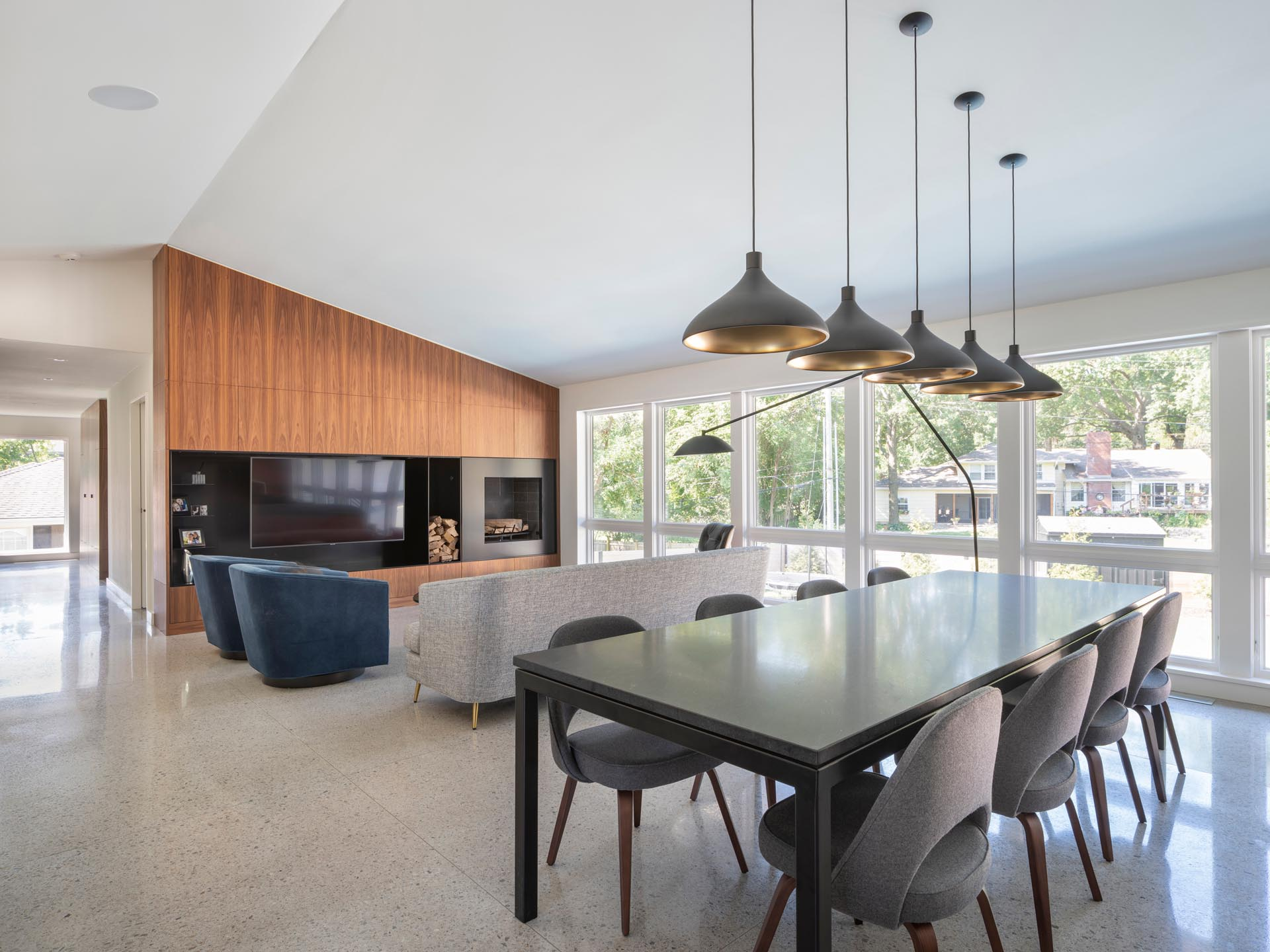 Inside, the main social areas of the house are open plan, with the dark dining table separating the living room from the kitchen.