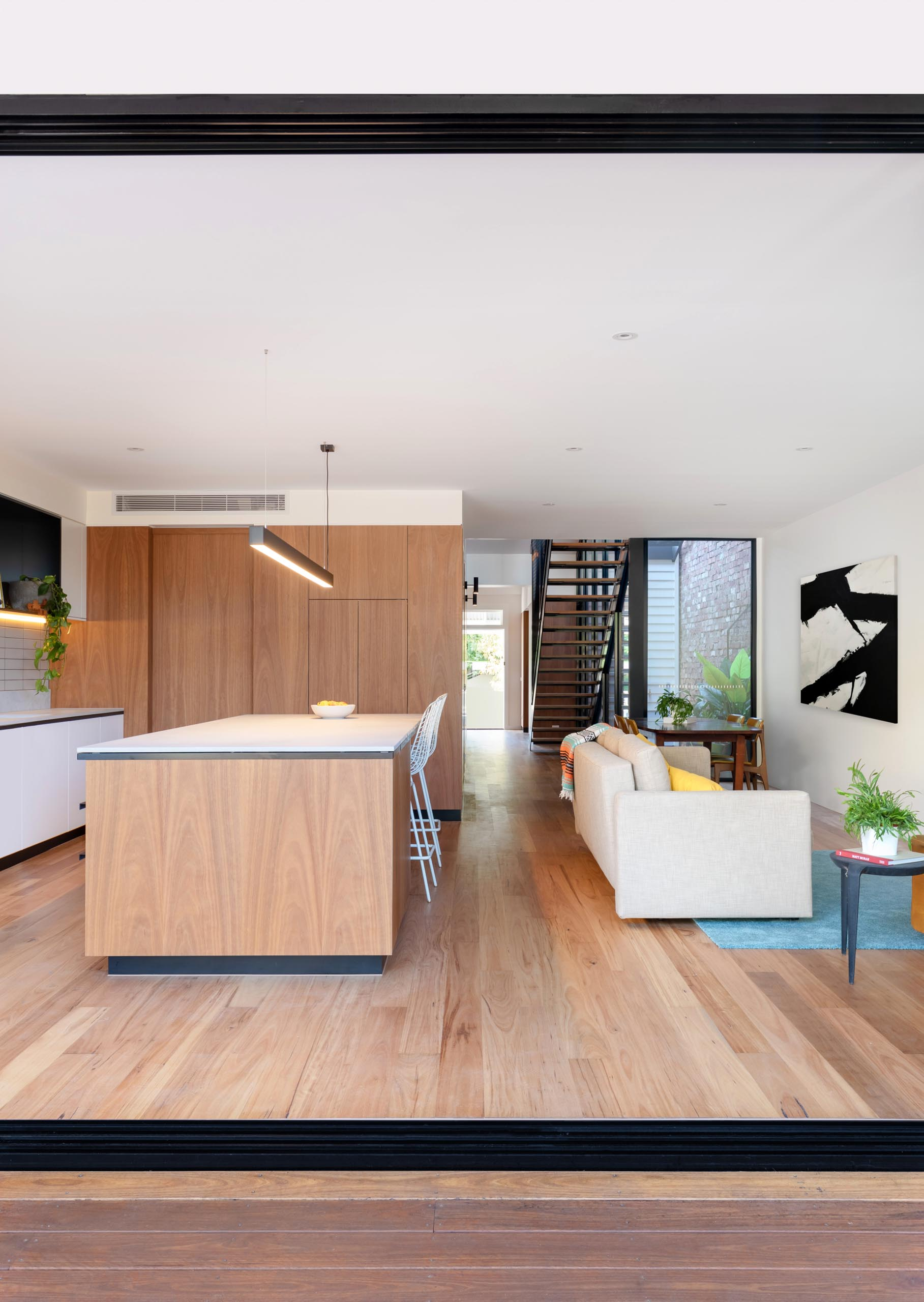 A modern open plan interior with wood flooring.