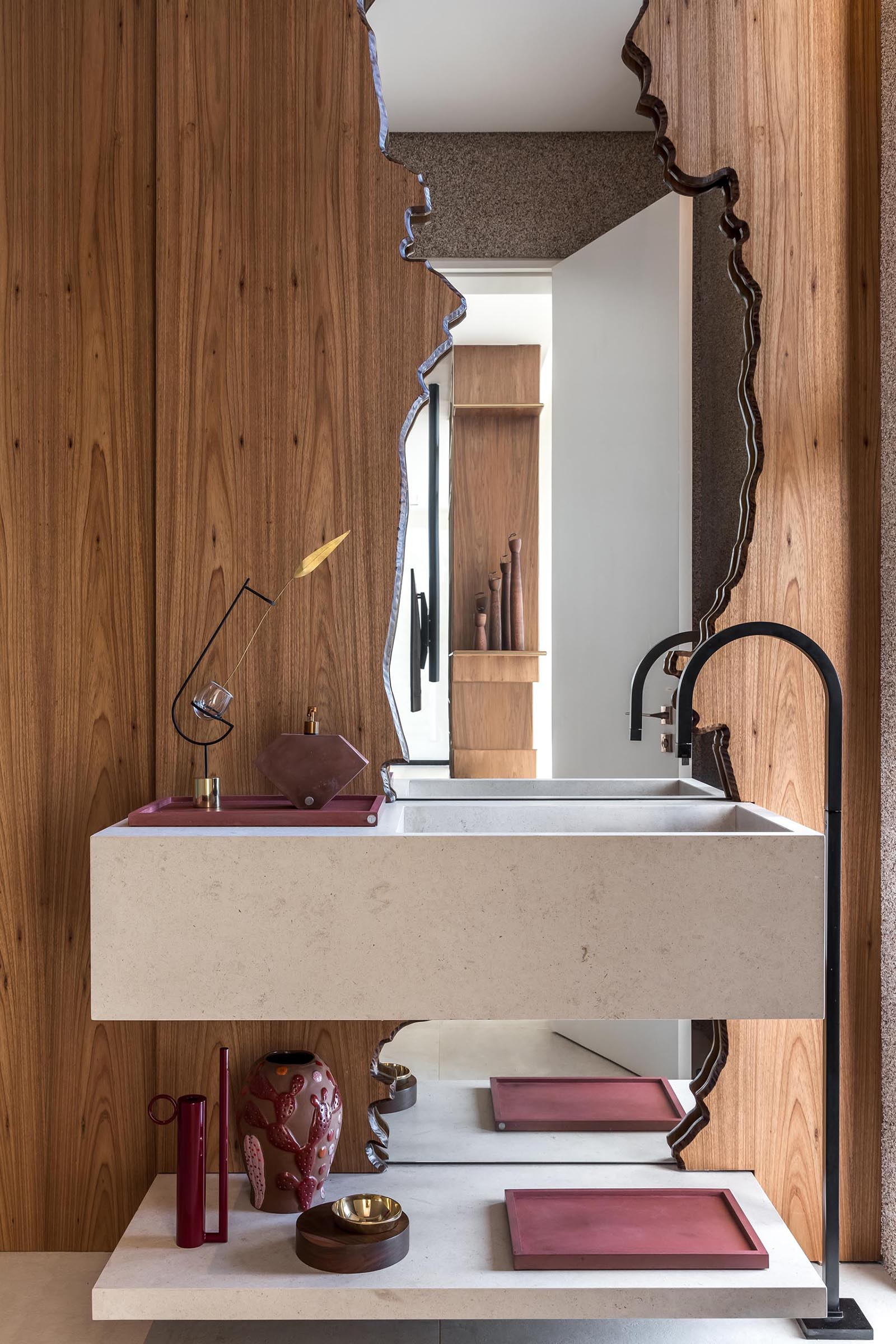 In a powder room, there's a mirror framed by floor-to-ceiling wood.