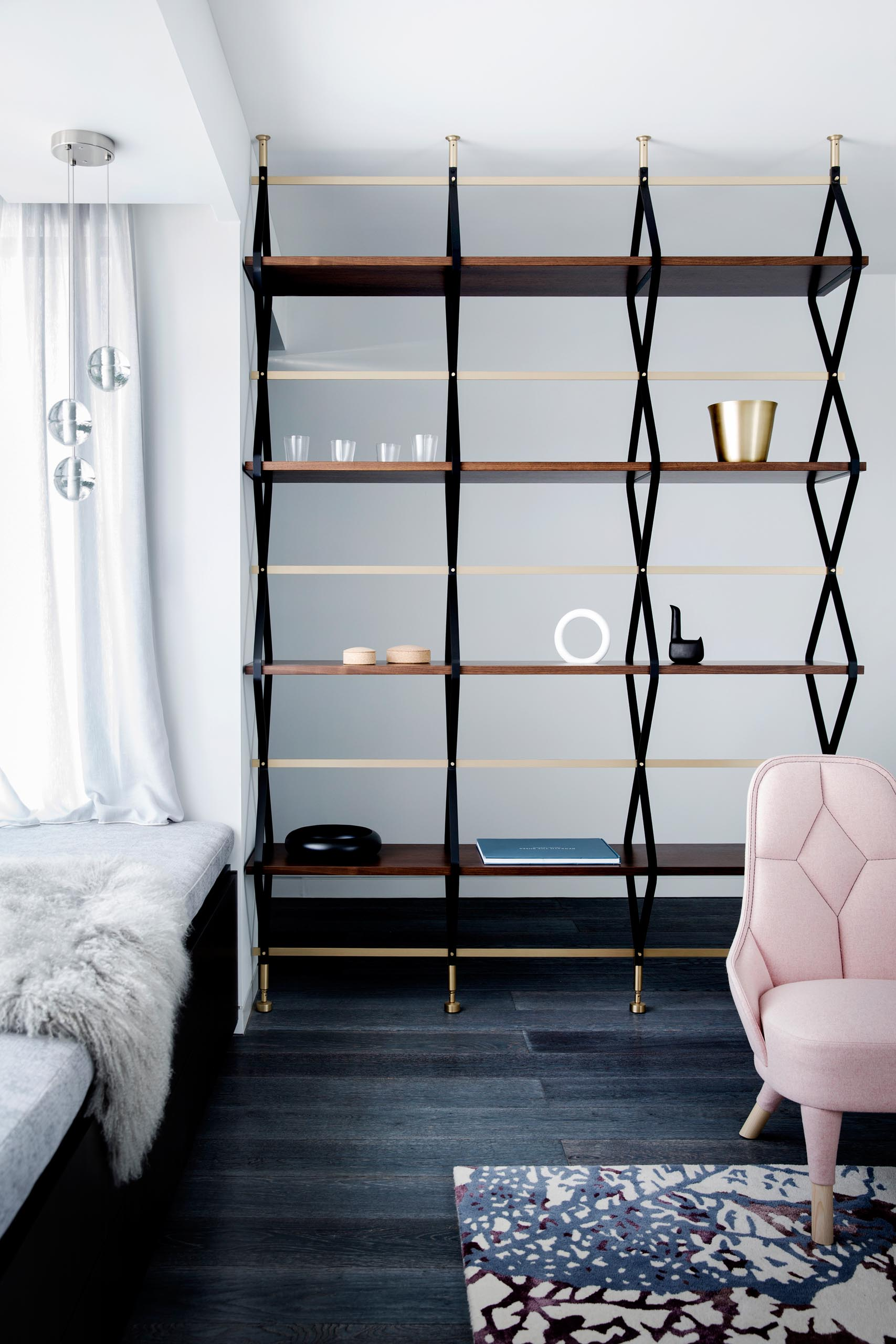 A modern and open shelving unit that acts as a room divider between the living room and entryway.