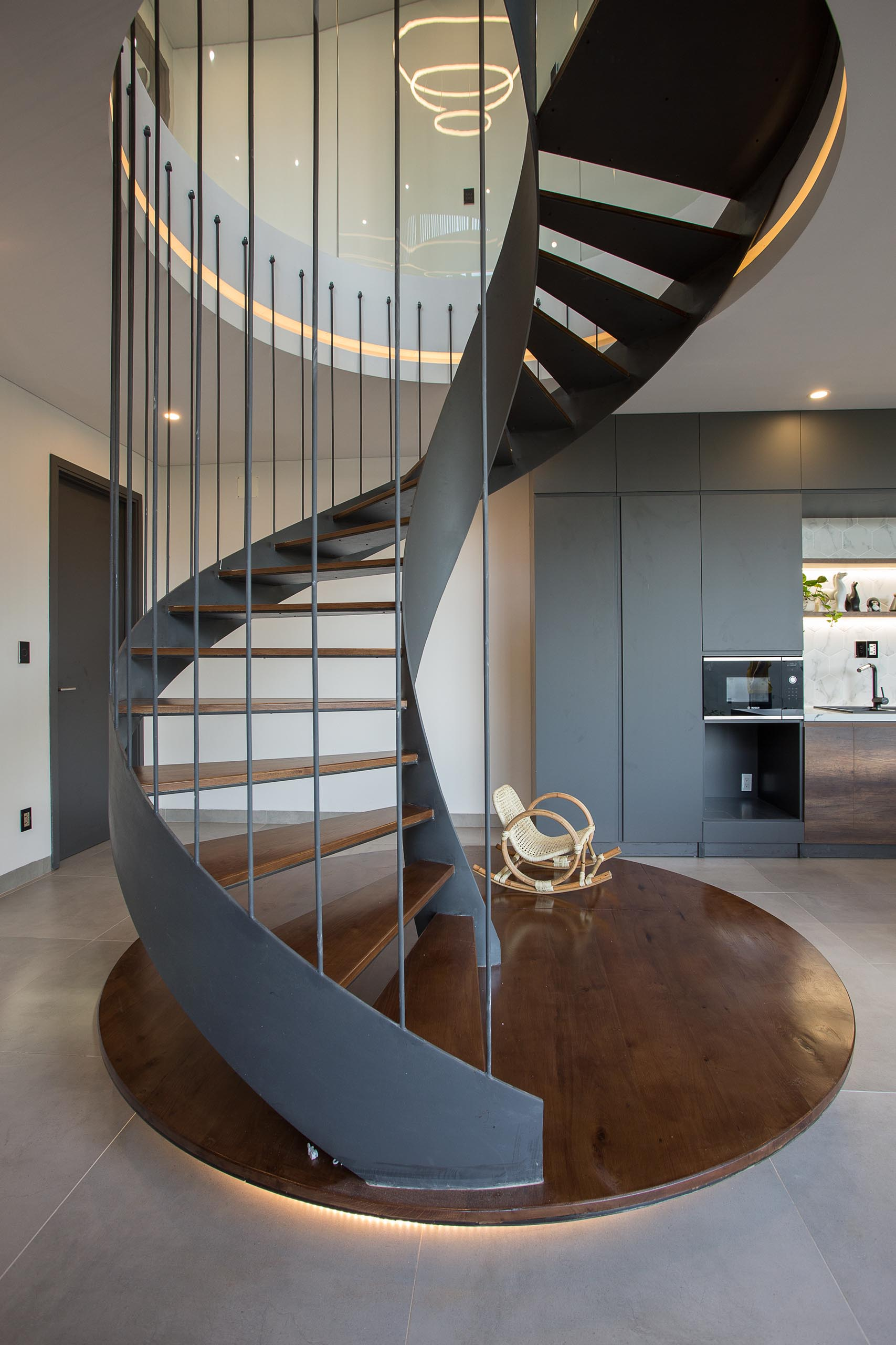 A modern home with black spiral stairs.