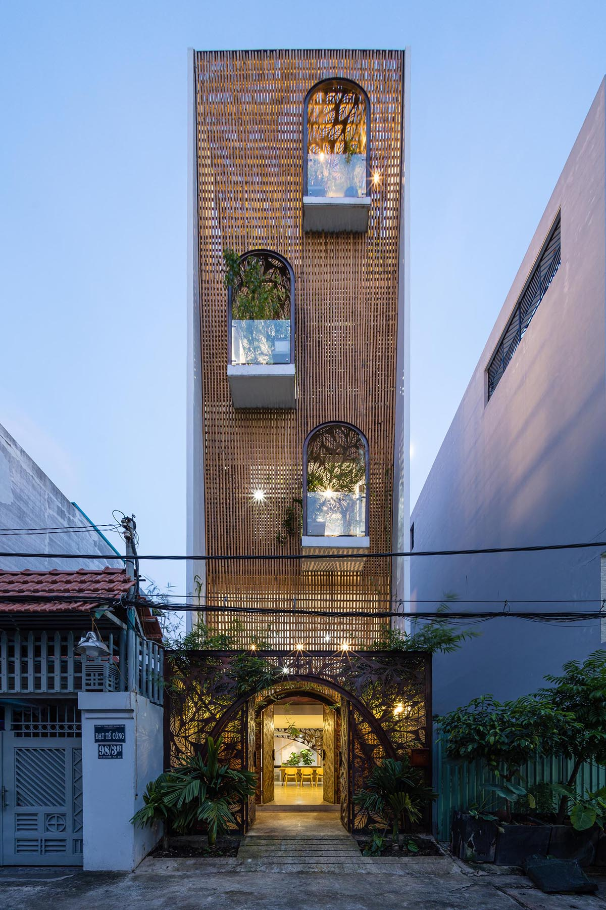 A modern home in Vietnam that has decorative metal screens with a leaf motif.