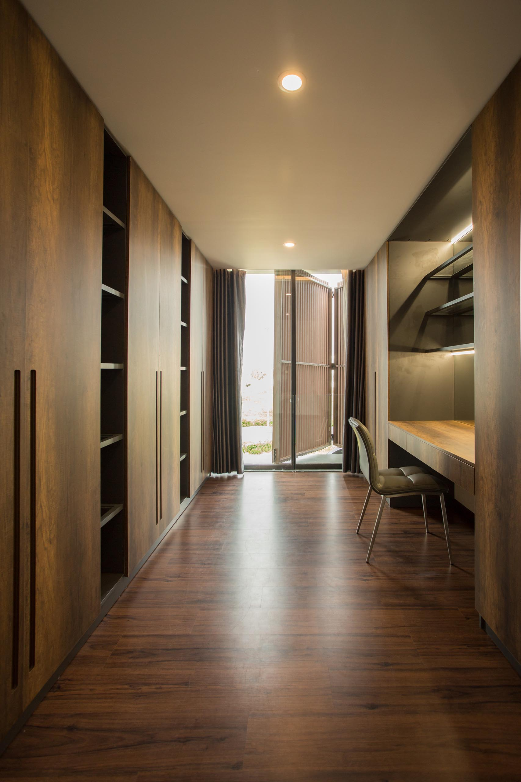 A walk-in closet with dark wood cabinets and a dedicated desk/vanity area.