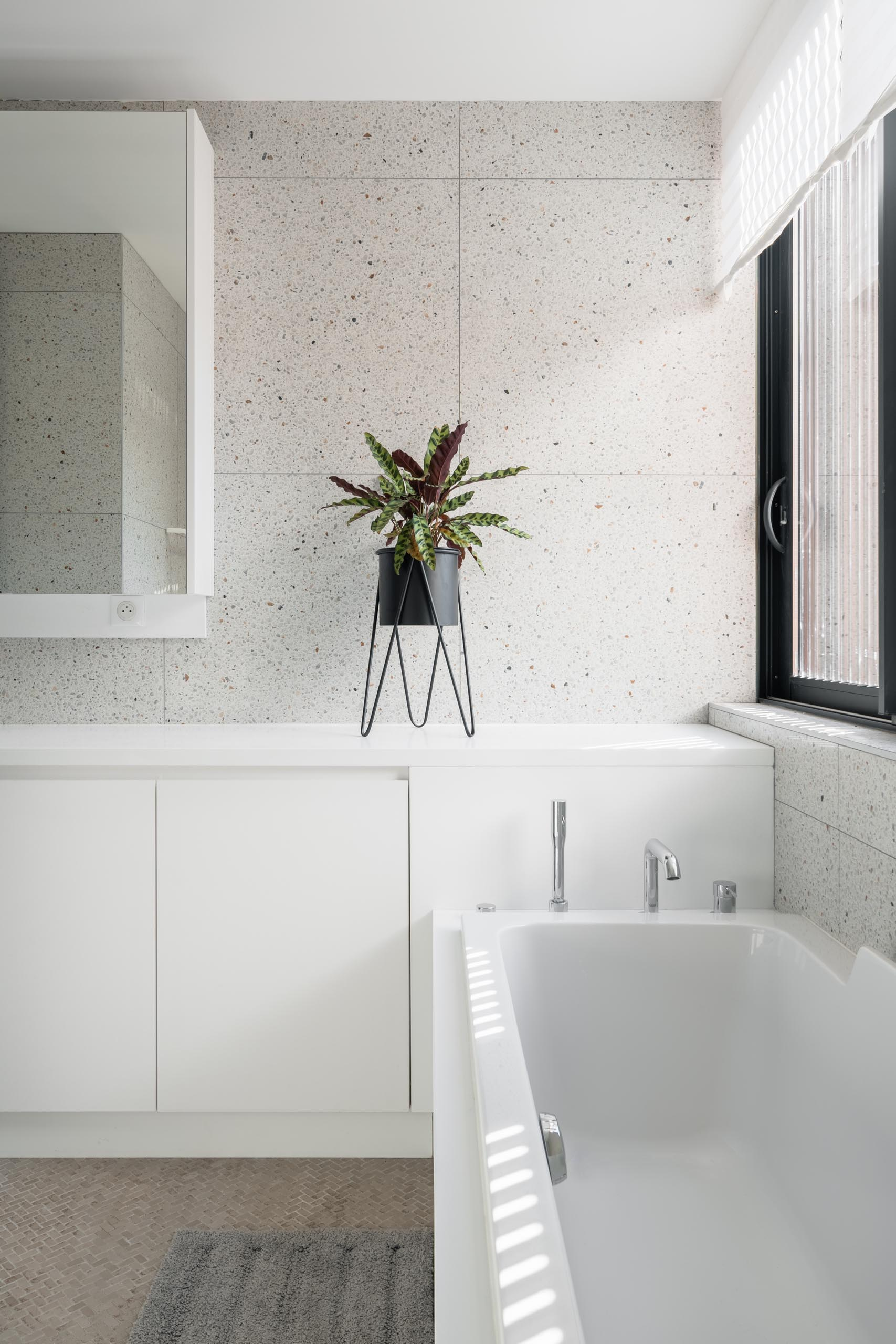 A modern bathroom with light colored walls, white cabinetry, a  large mirror, and built-in bathtub.