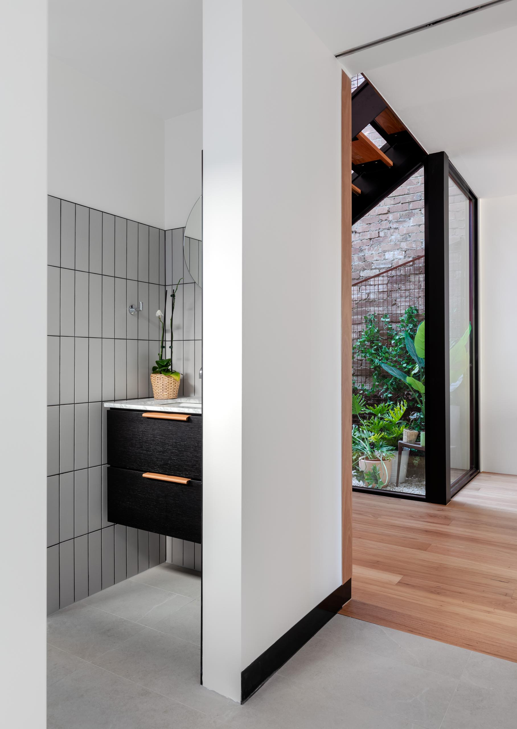 A modern bathroom with light gray rectangular tiles and a black vanity.
