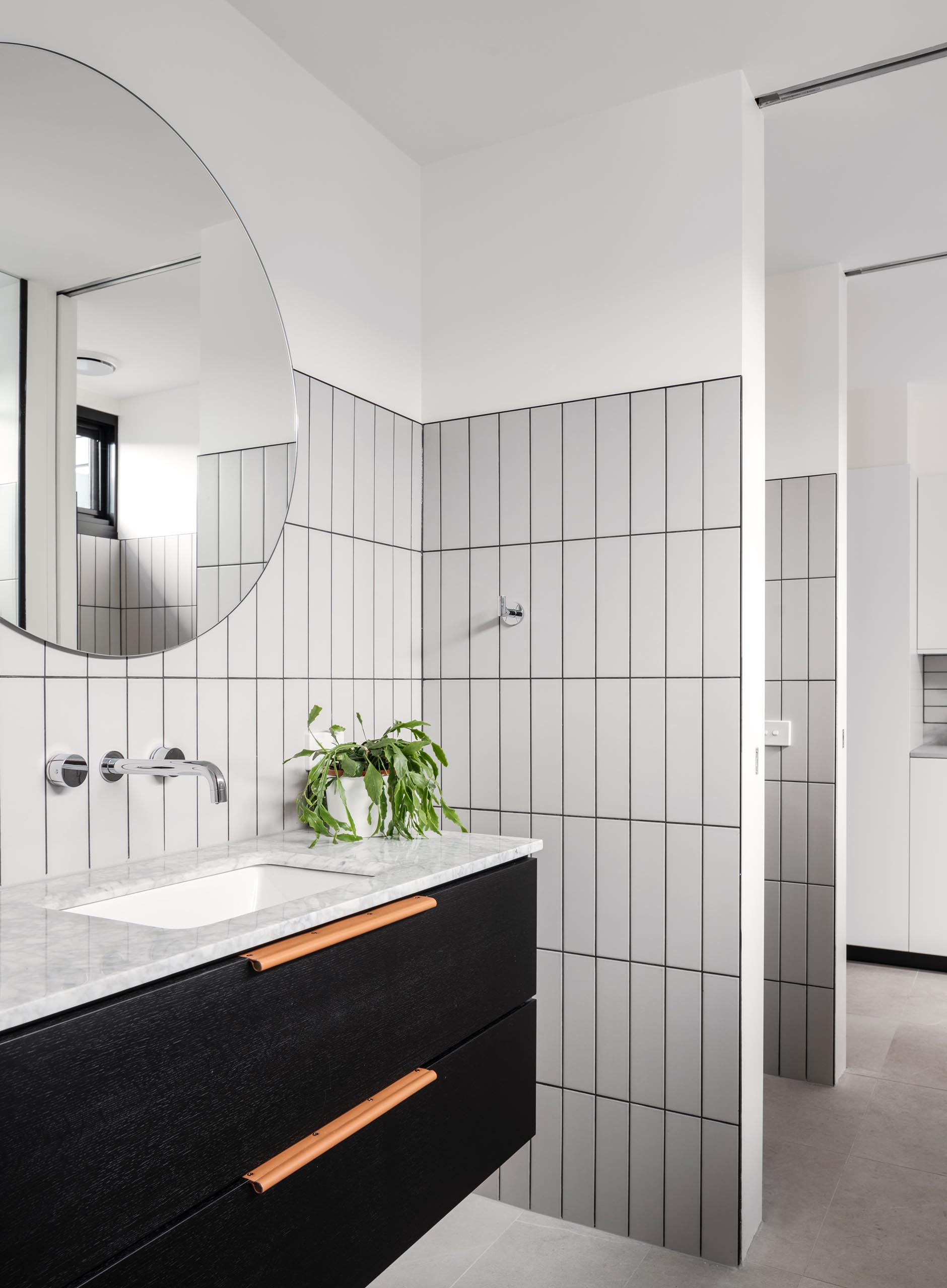 In the bathroom, rectangular light gray tiles with dark grout have been laid in a vertical pattern, while a black vanity sits below a round mirror.