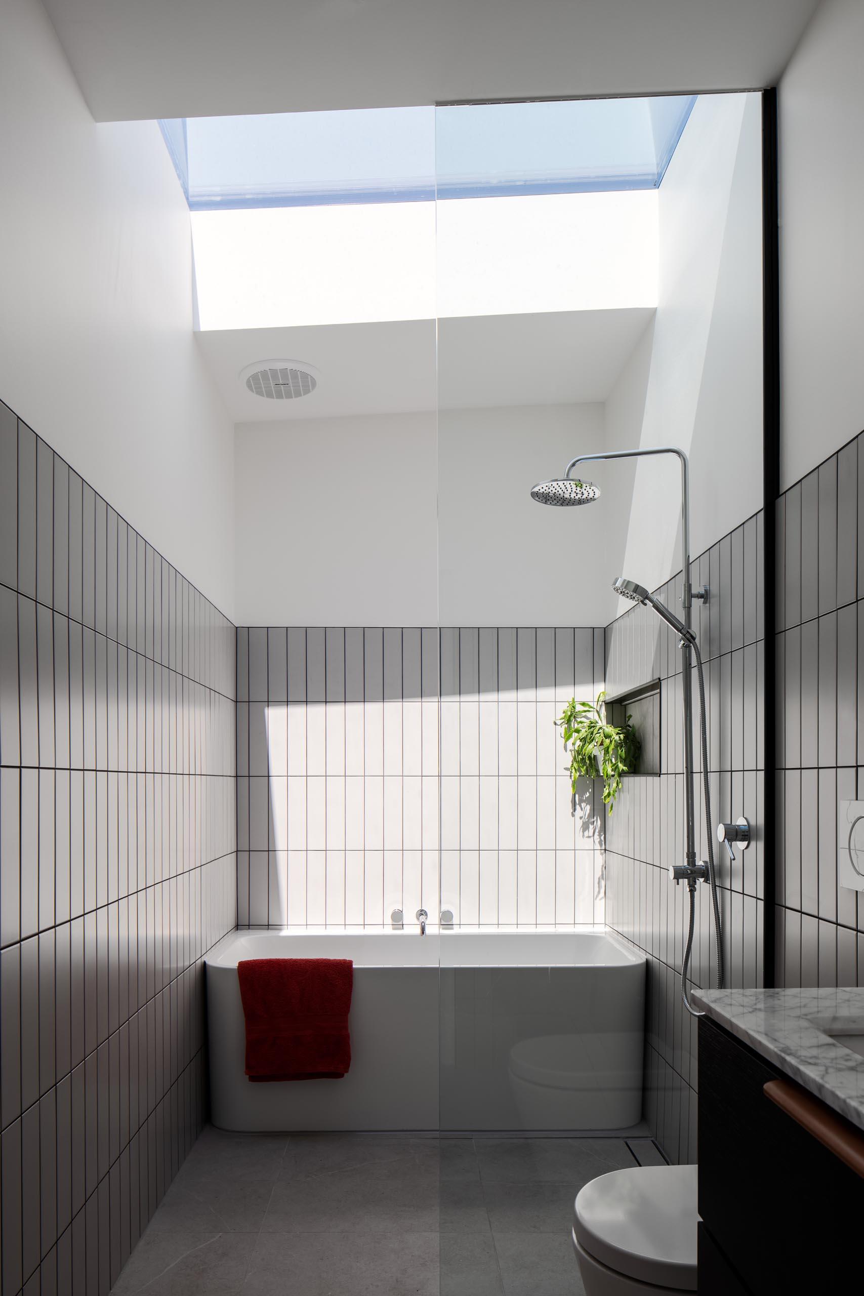 A modern bathroom with gray tiles, a white bathtub, and a skylight.