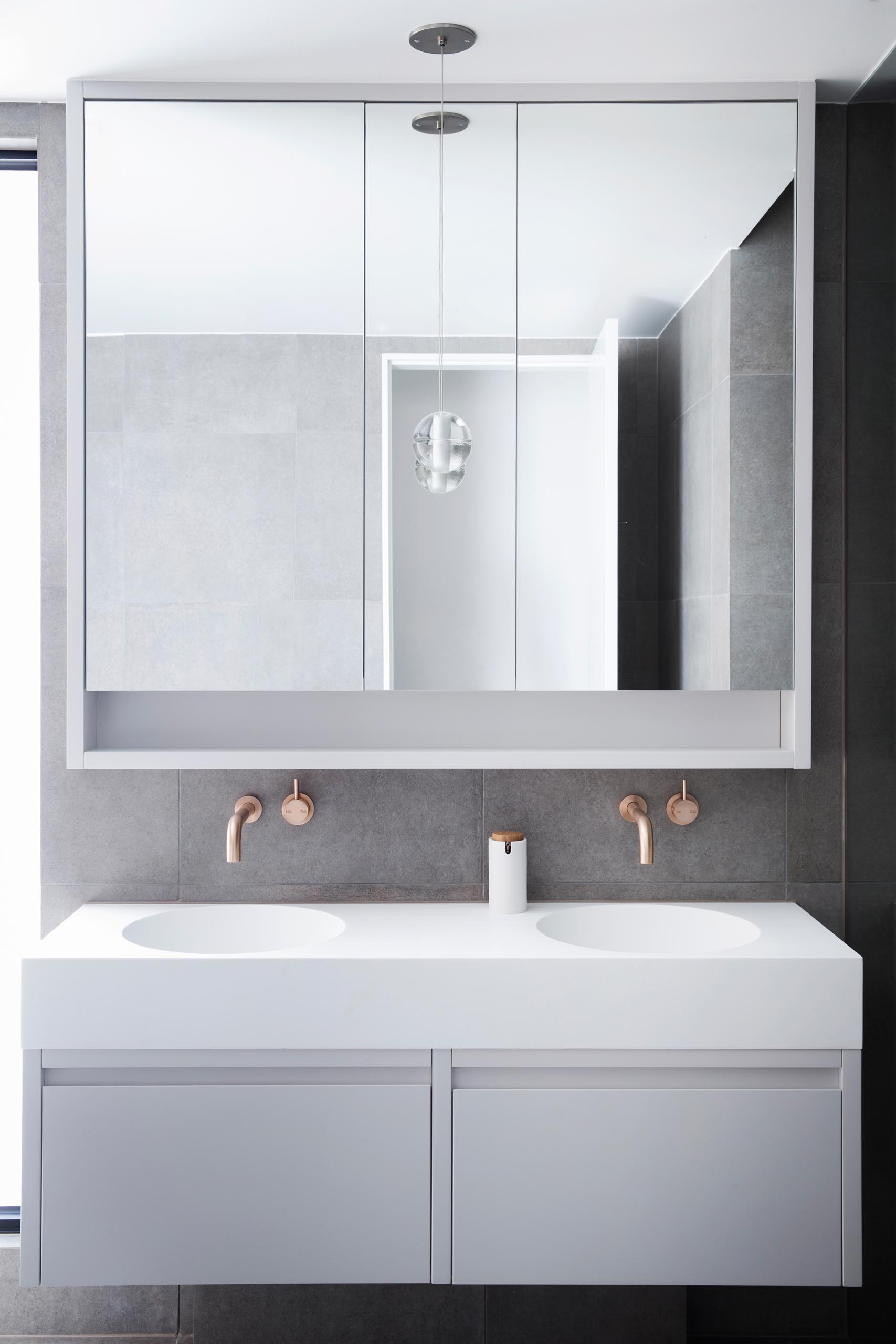 A modern bathroom with a large mirror, brushed rose gold hardware, a countertop with dual built-in sinks, and minimalist cabinetry.