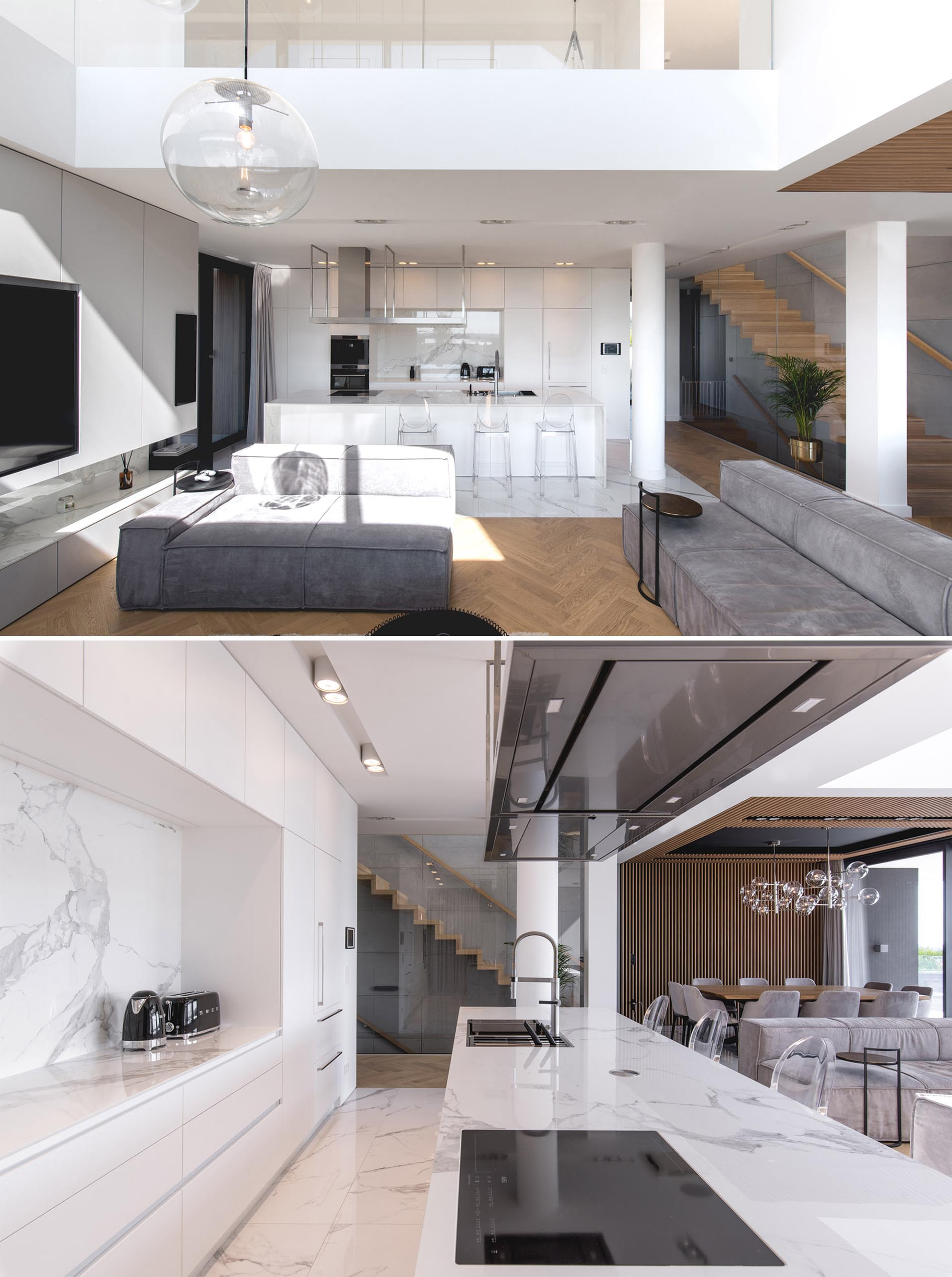 A modern kitchen with minimalist white cabinets that line the wall, and a large island adds extra counter space.