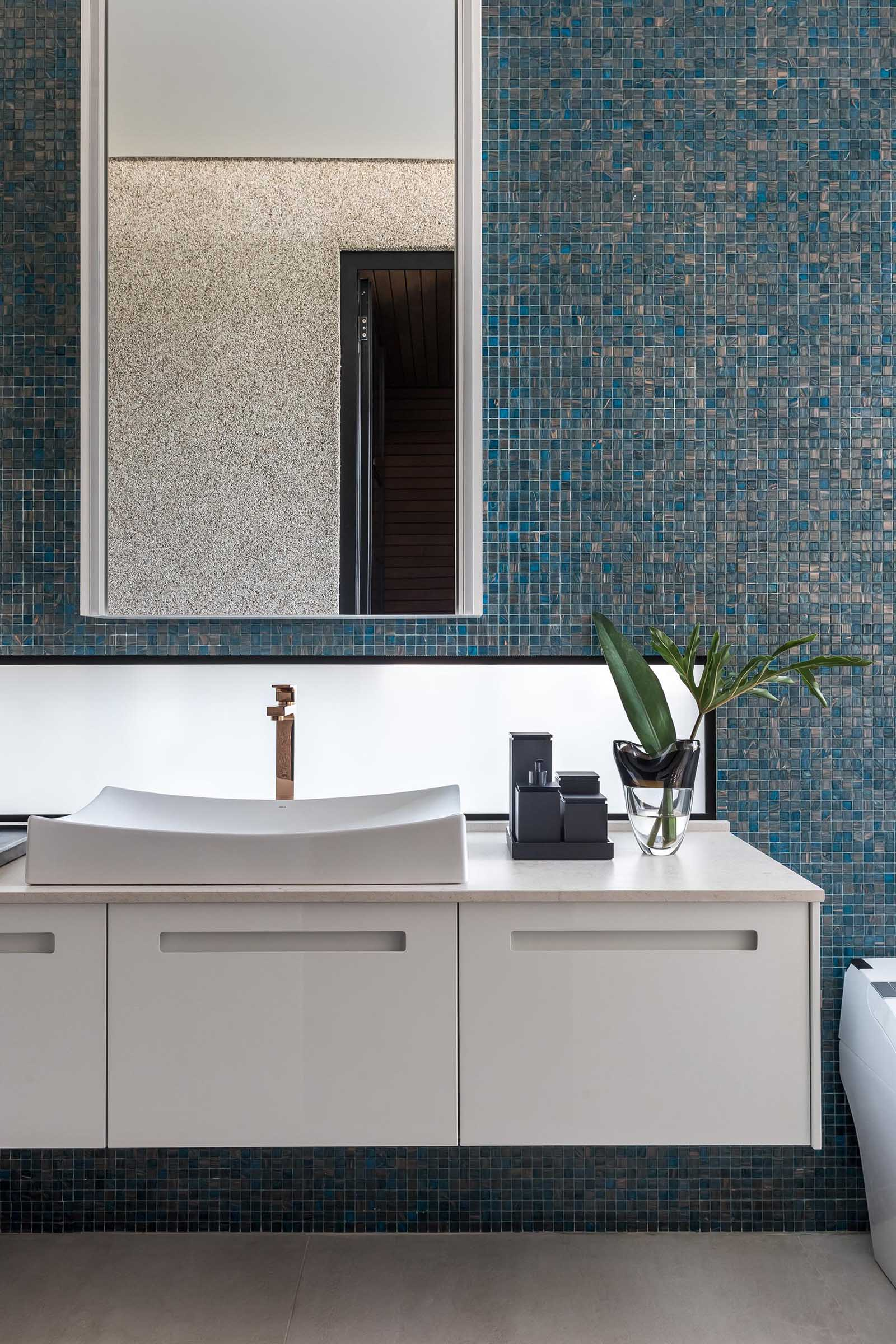A blue tiled accent wall provides a backdrop for the white vanity and mirror in this modern bathroom.