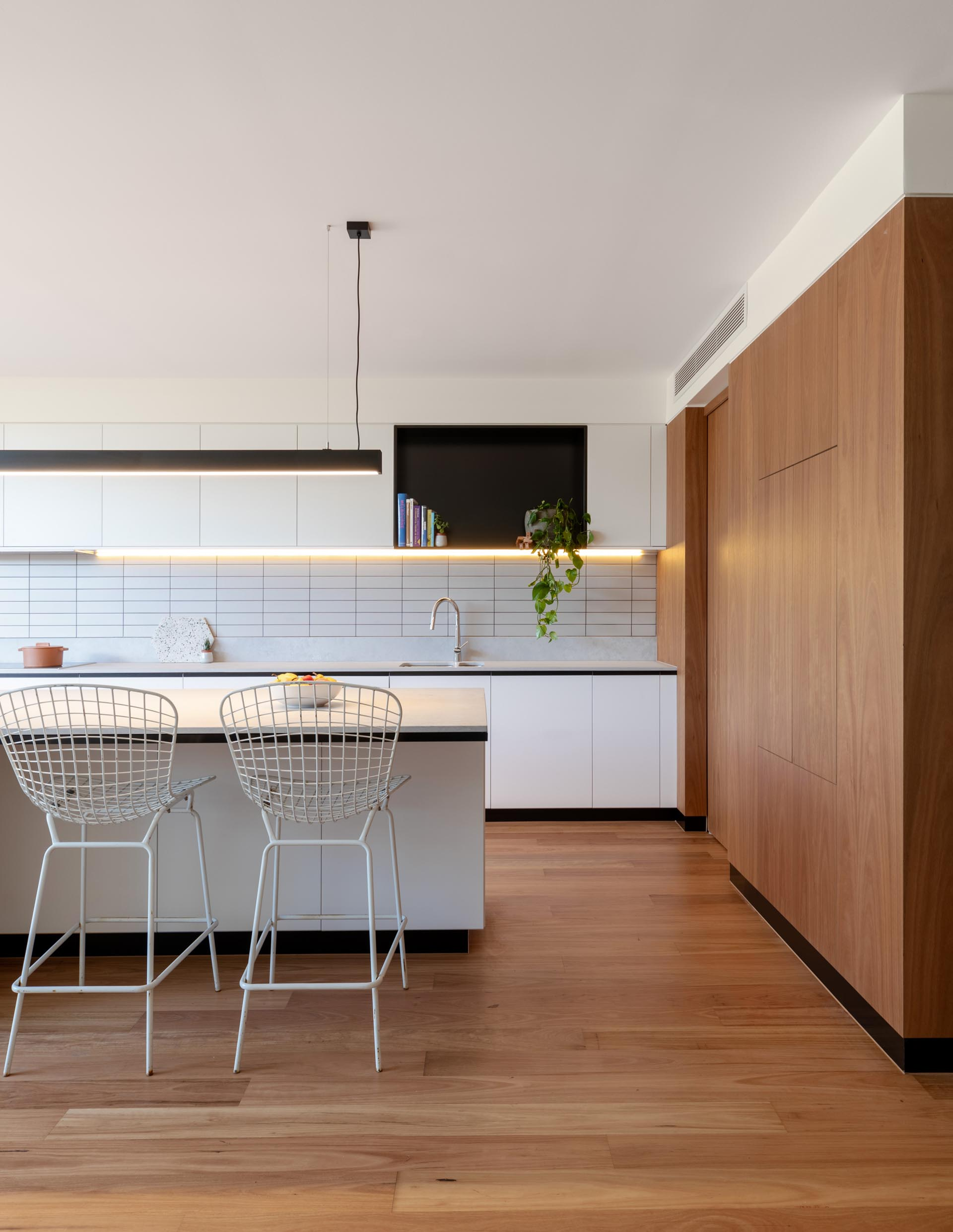 A modern kitchen includes minimalist white cabinets, a black accent shelf, a large island with room for seating, and undermount lighting.