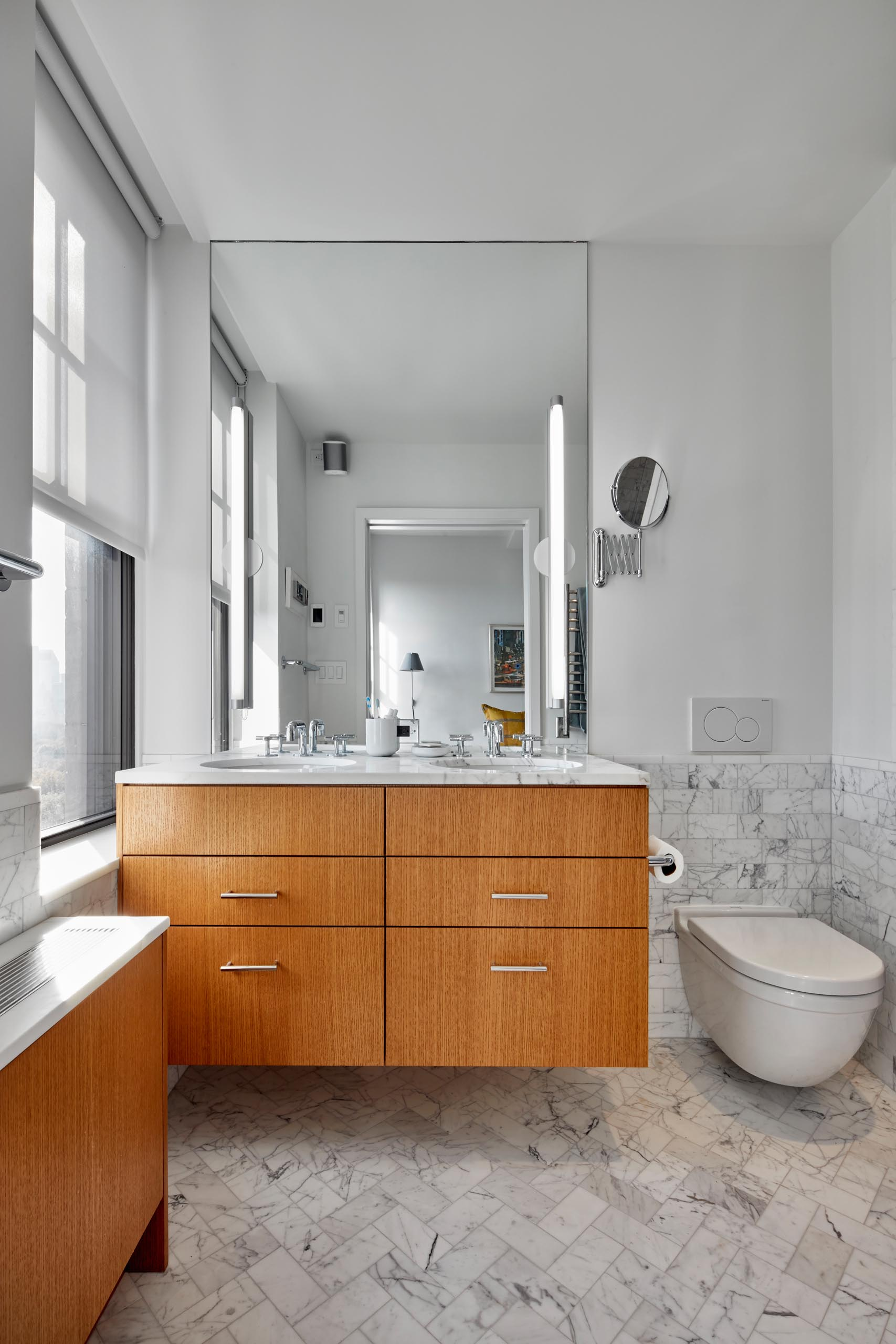 A modern bathroom with a wood vanity and radiator cover, and marbled tiles.