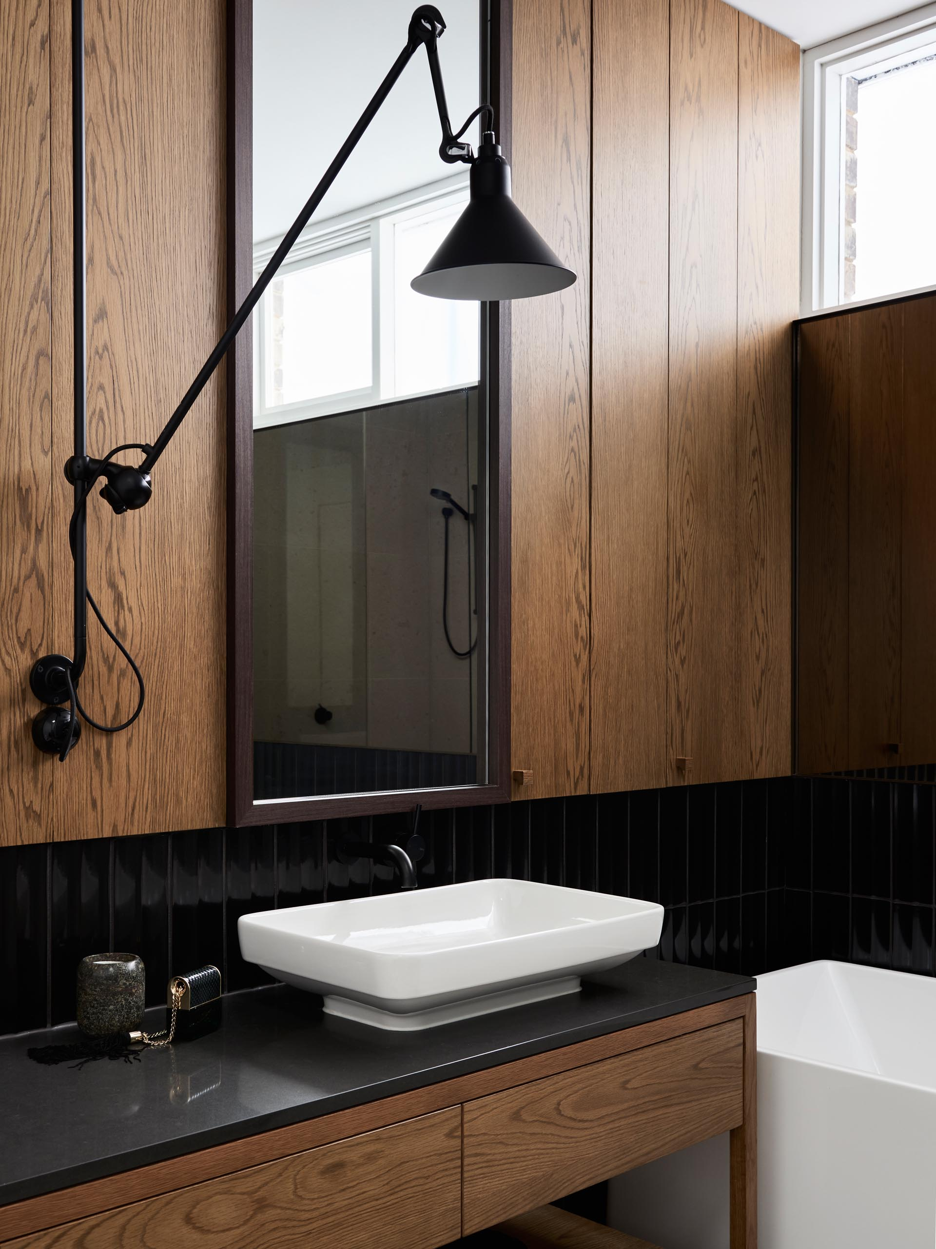 In this modern bathroom, wood paneling and a wood vanity have been paired with black tiles, a white vanity, and white bathtub.