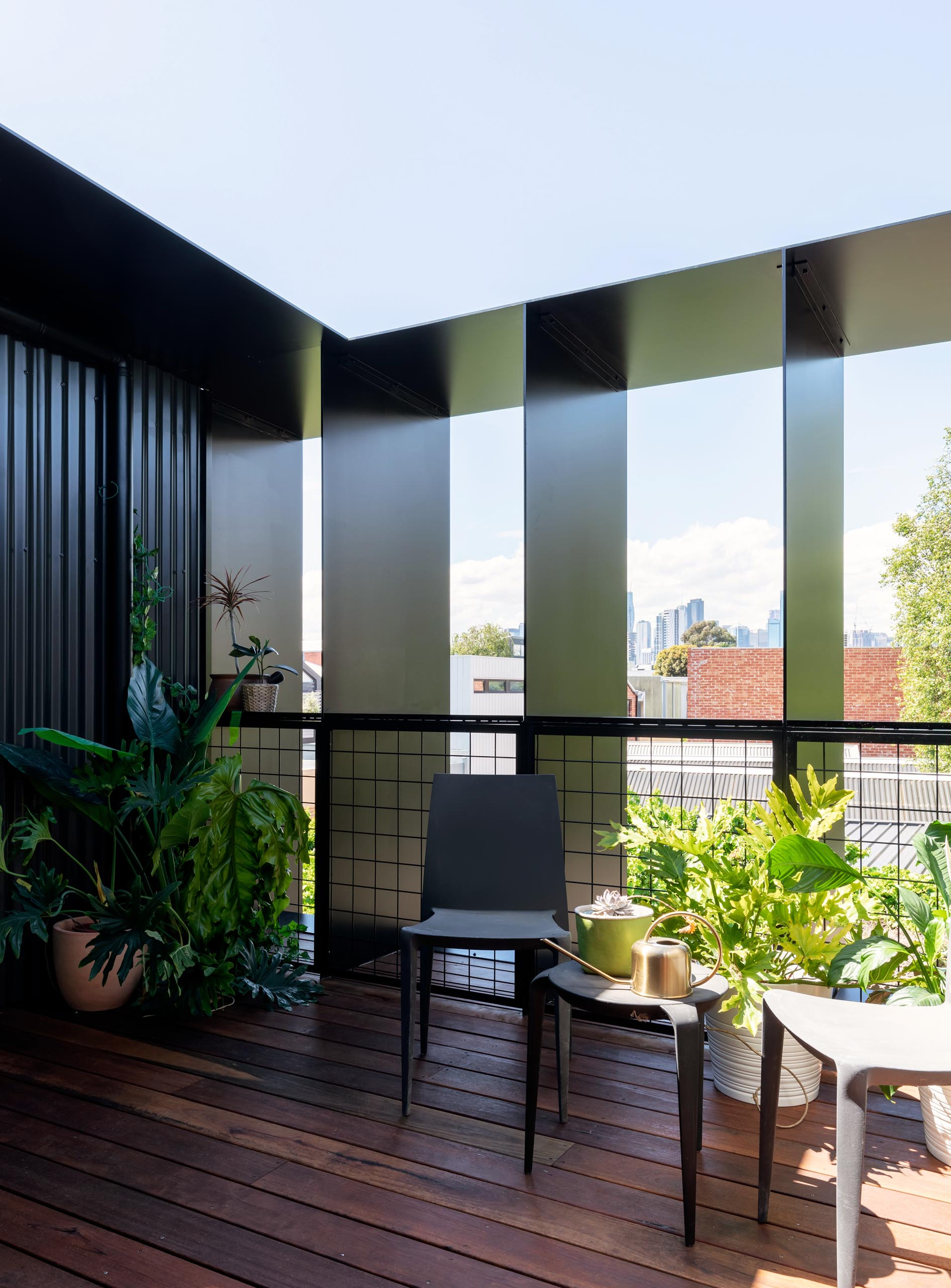 A semi-private deck with wood flooring and corrugated metal siding.