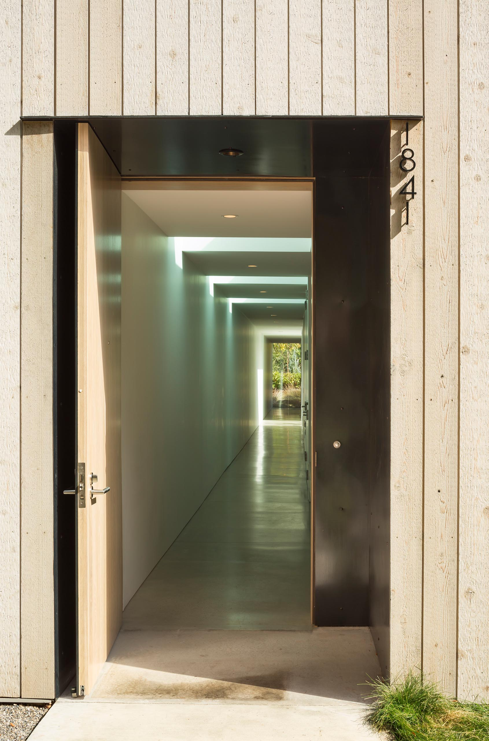 A modern cedar clad home with a black front door and long hallway.