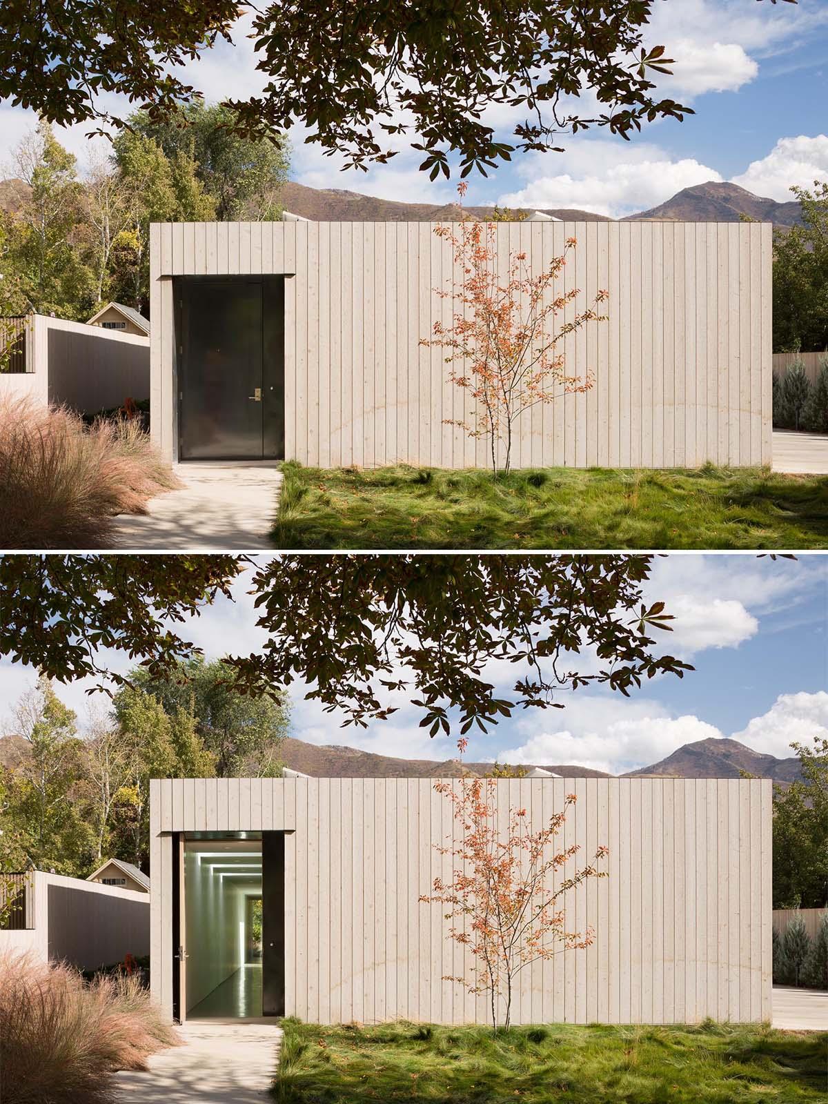 A modern cedar clad home with a black front door.