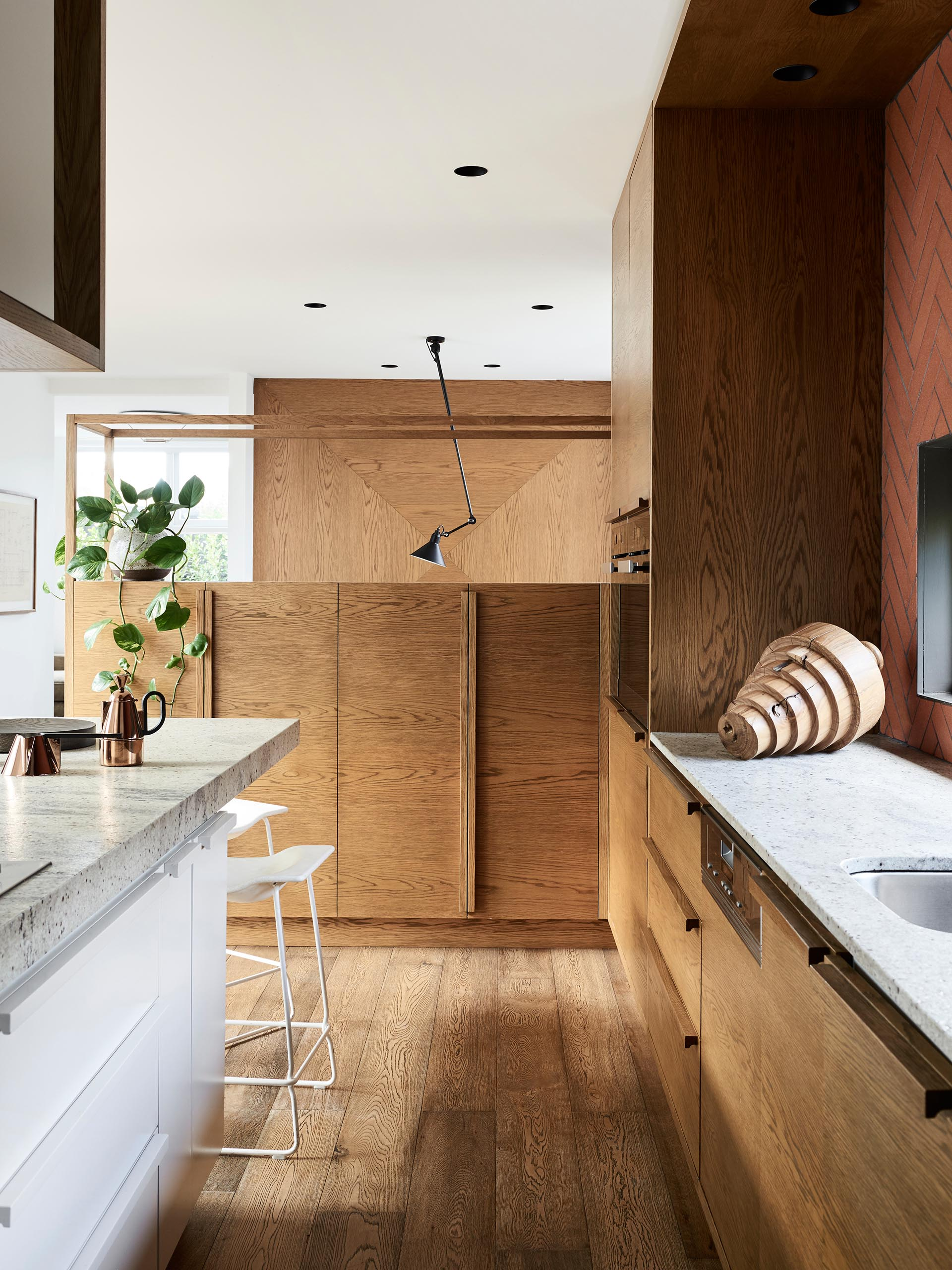 This kitchen has minimalist wood and white cabinets have been paired with a long island, and a terracotta colored tile backsplash that surrounds the window.
