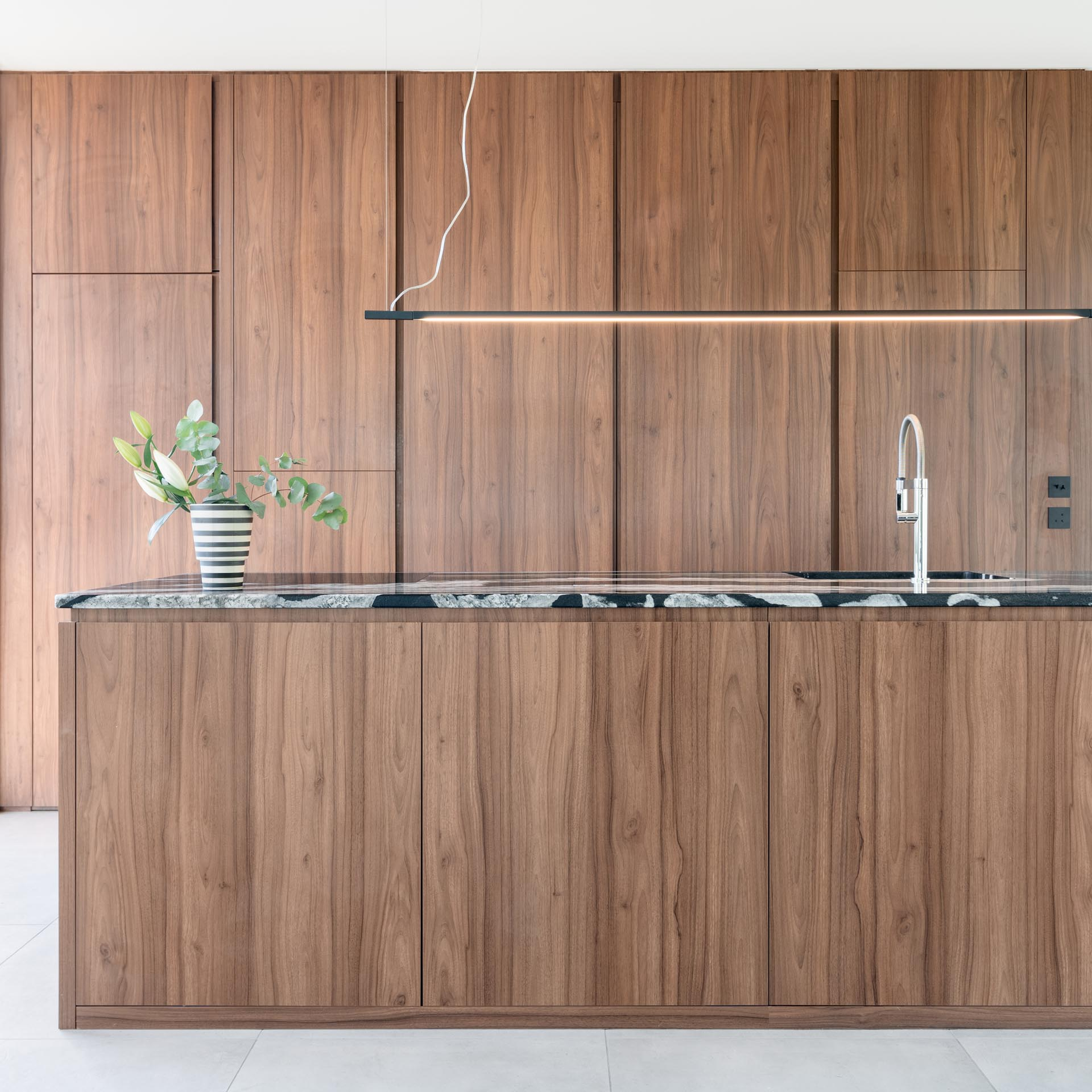In this modern kitchen, minimalist warm wood cabinets have been used along the wall and the island.