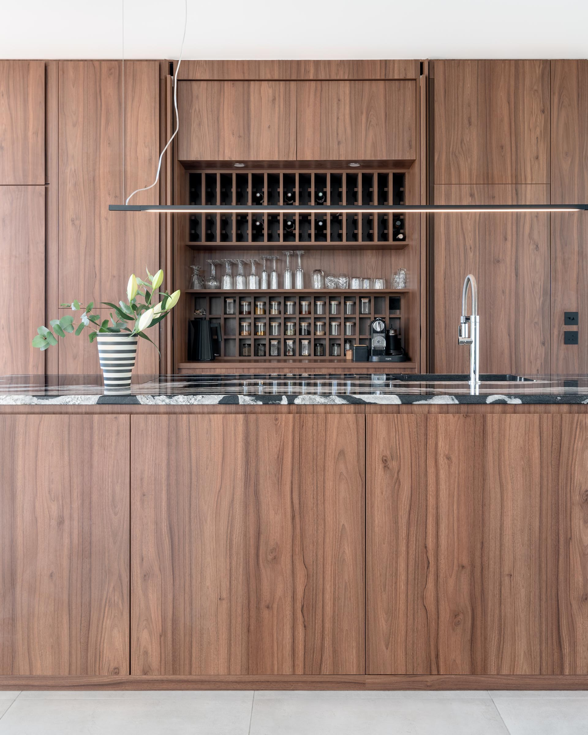 In this modern kitchen, minimalist warm wood cabinets have been used along the wall and the island. Hidden within a pair of the hardware free cabinets are shelving that's designed to hold wine bottles, glassware, and spice jars.