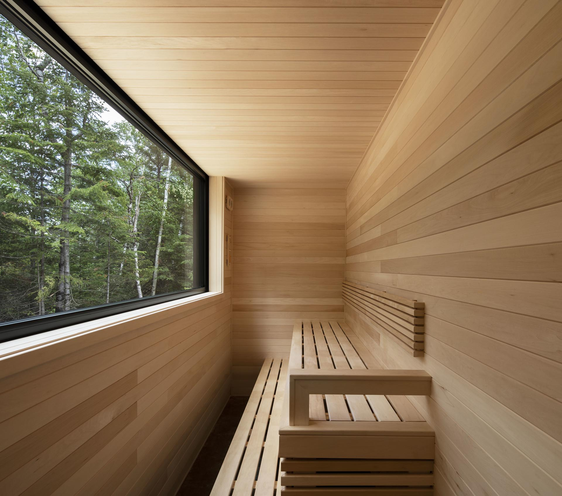 A modern wood-lined sauna with a large window.