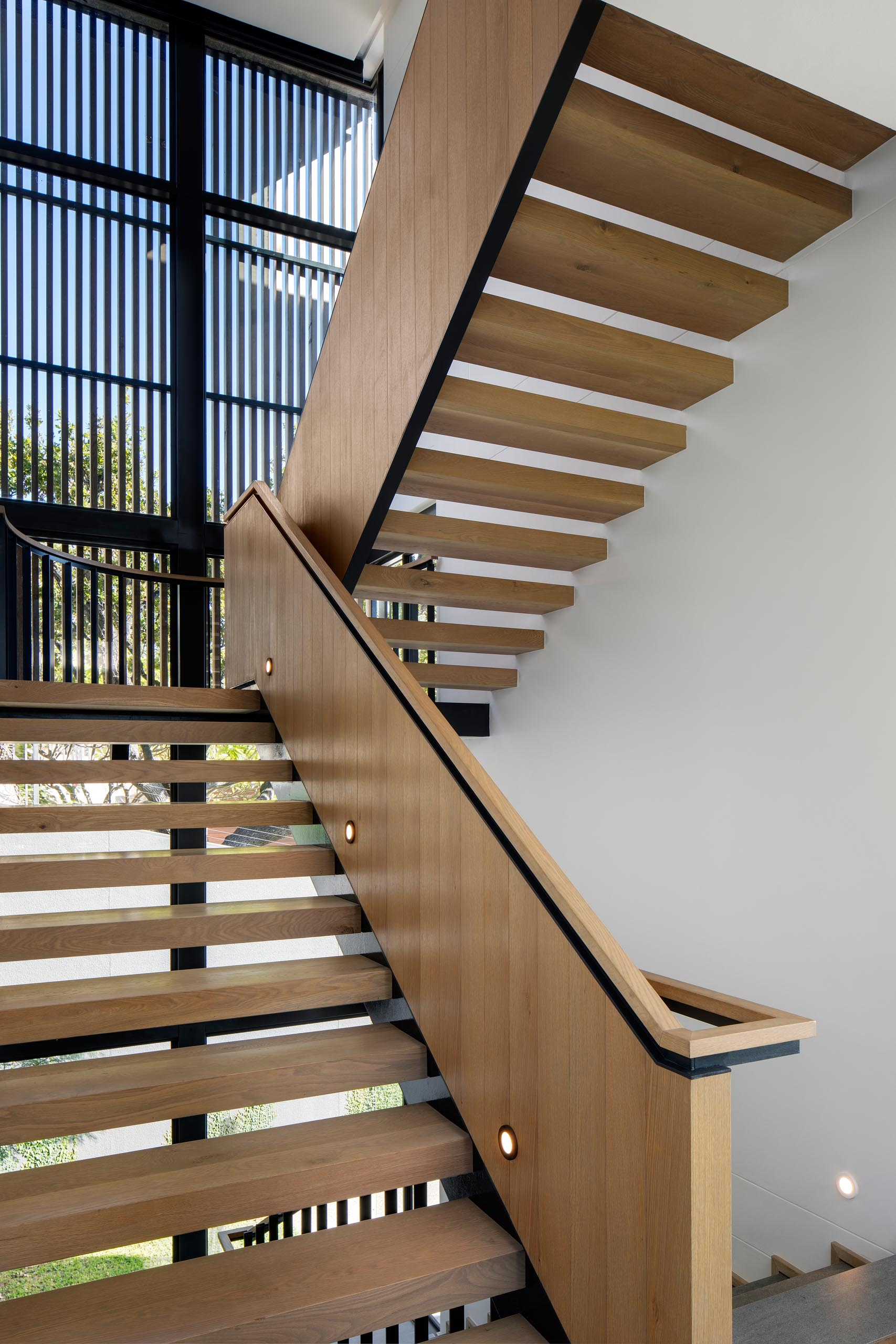 A modern wood staircase with black accents.