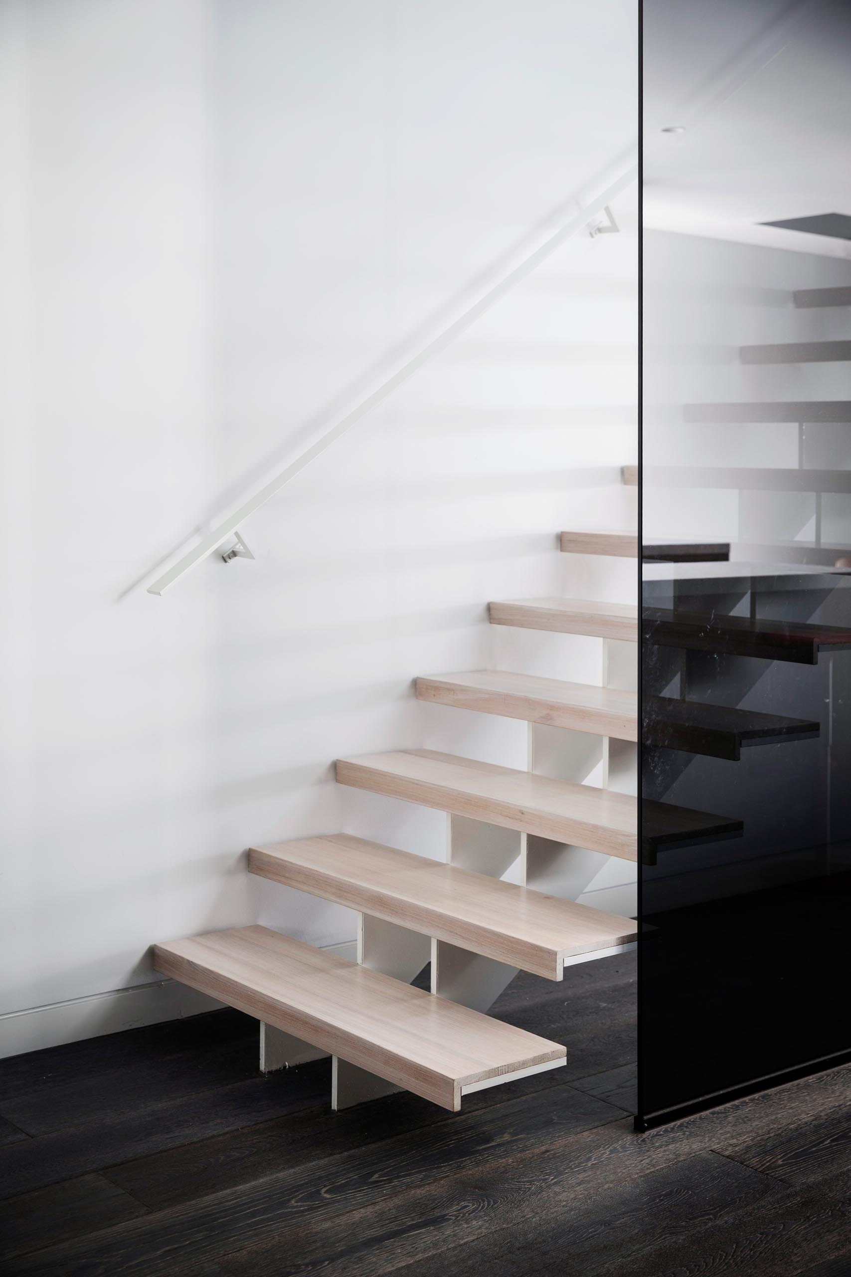 Modern light wood stairs with a white steel support and matching handrail.