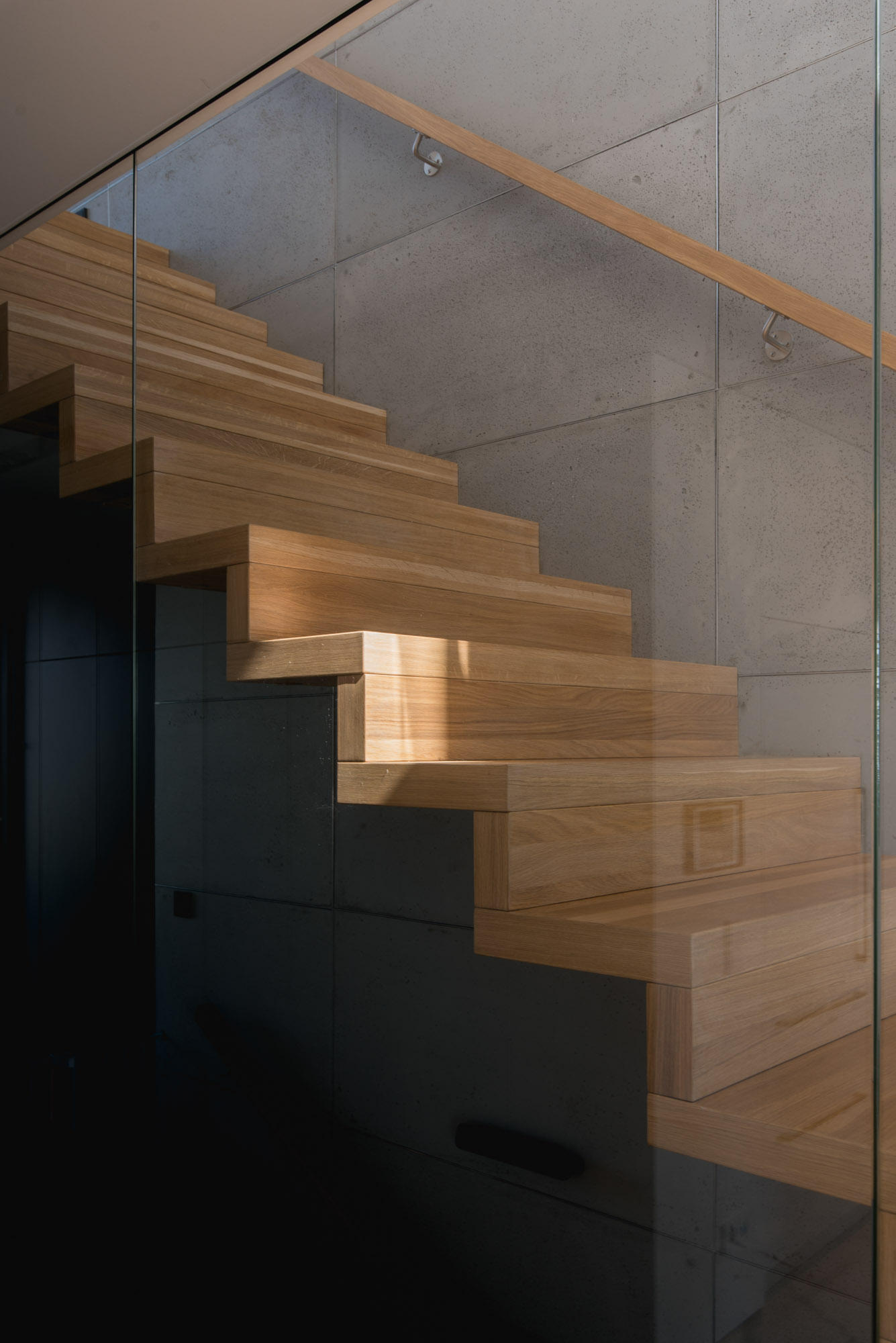 Wood stairs behind a glass wall lead from the social areas of this modern house to the upper floor.