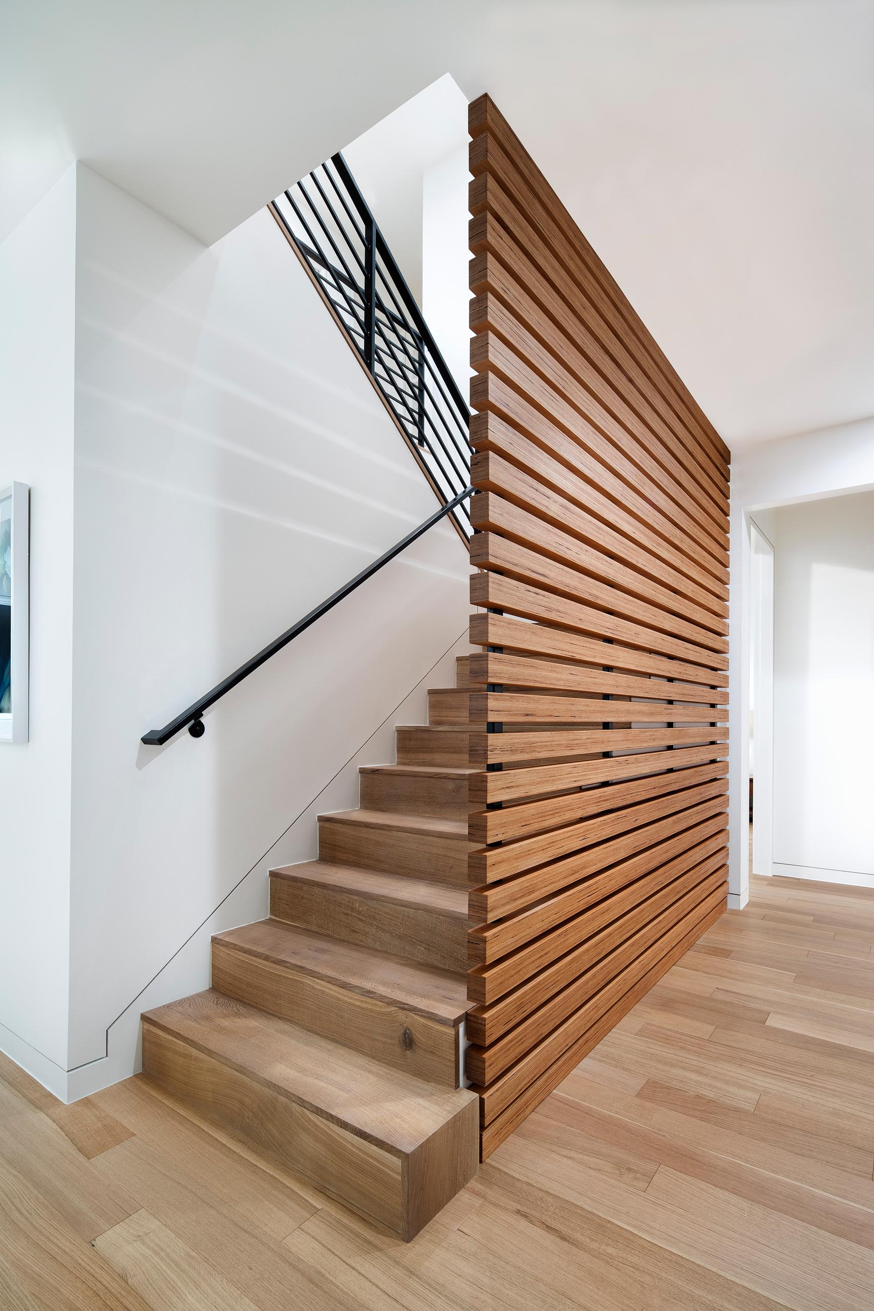 Modern wood stairs with a matching screen and black handrail.