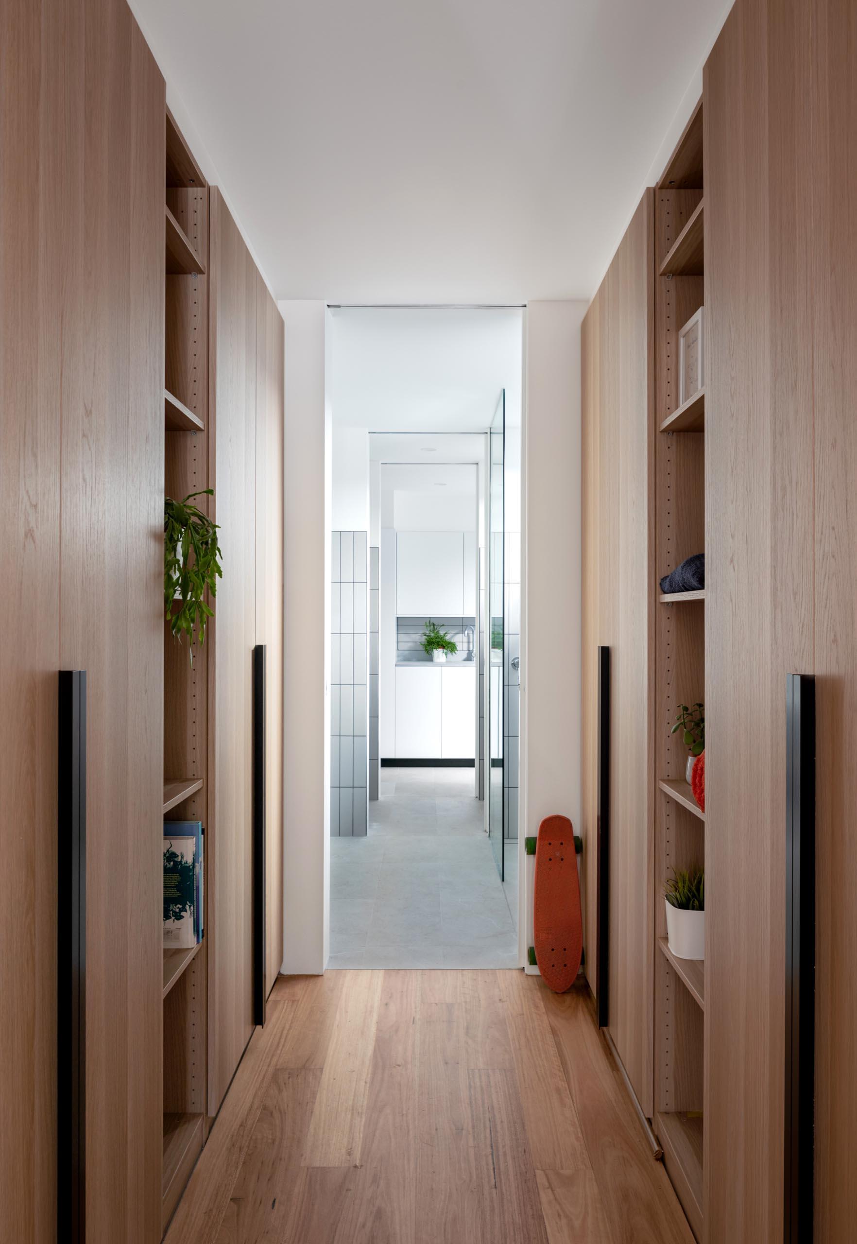 A modern wood walk-through closet.