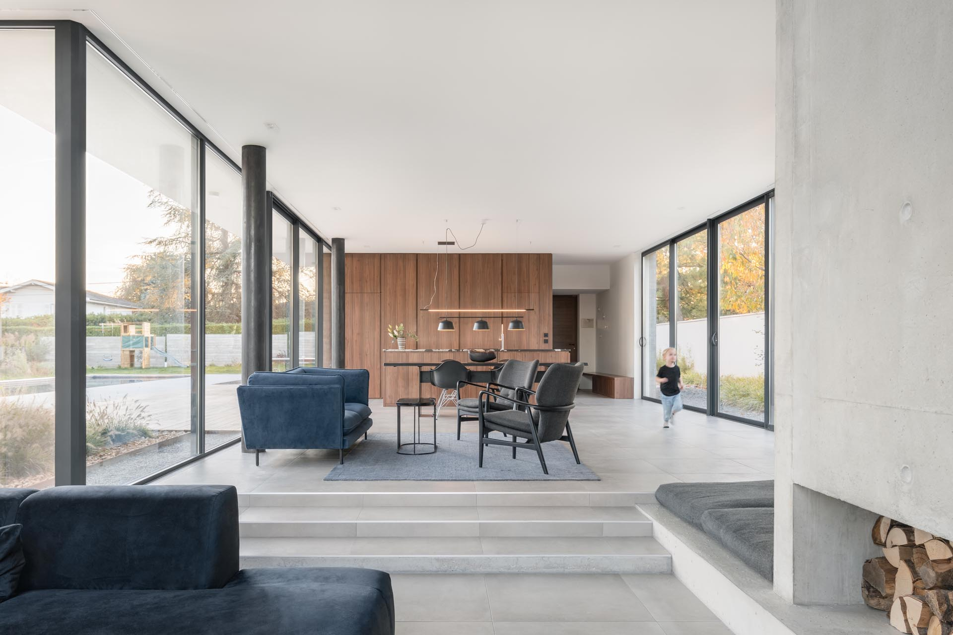 The living and dining areas of this modern home are open plan, with a few steps separating the two spaces. There's also a small ledge that's a dedicated space for a dog bed.