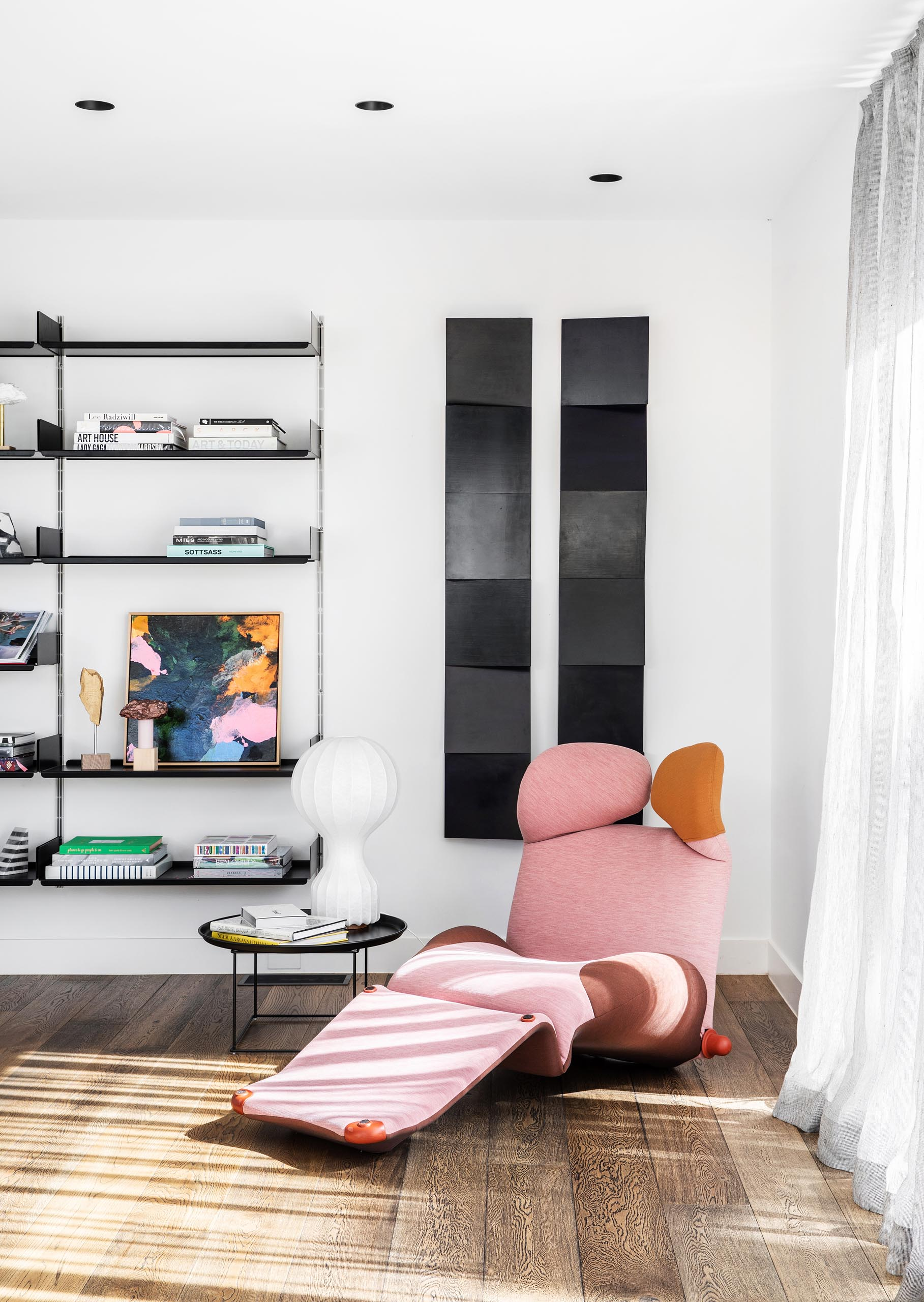 Tucked into the corner behind the living room is a small reading nook that includes a sculptural pink chaise, vertical art pieces, and a wall-mounted bookshelf.
