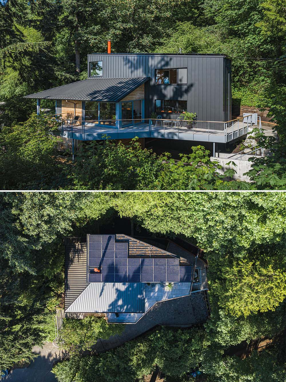 Located on a steep site, the updated black metal and wood exterior of this home is topped with solar panels on the roof.
