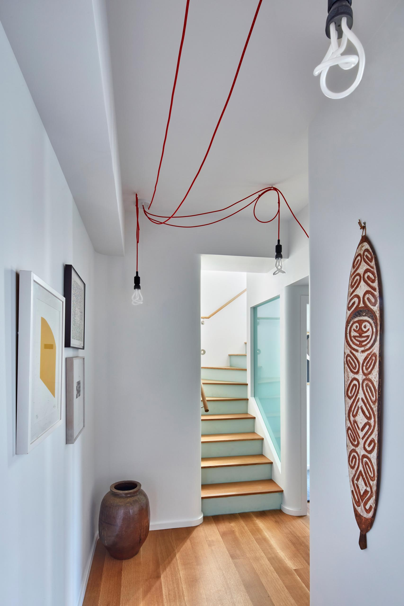 A staircase with wood treads opens up to a hallway with artwork.