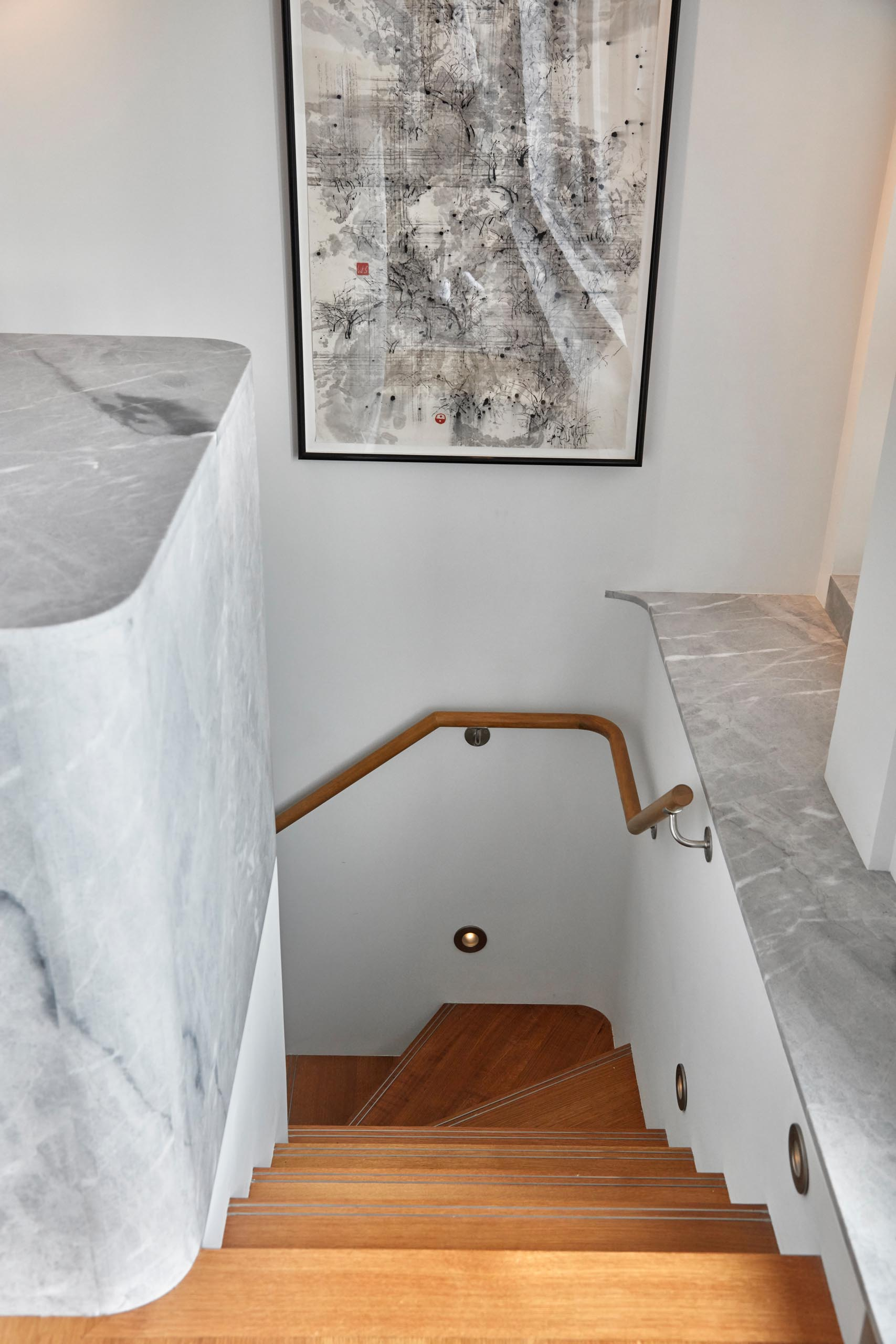 Contemporary stairs with wood treads and small lights built into the white walls.