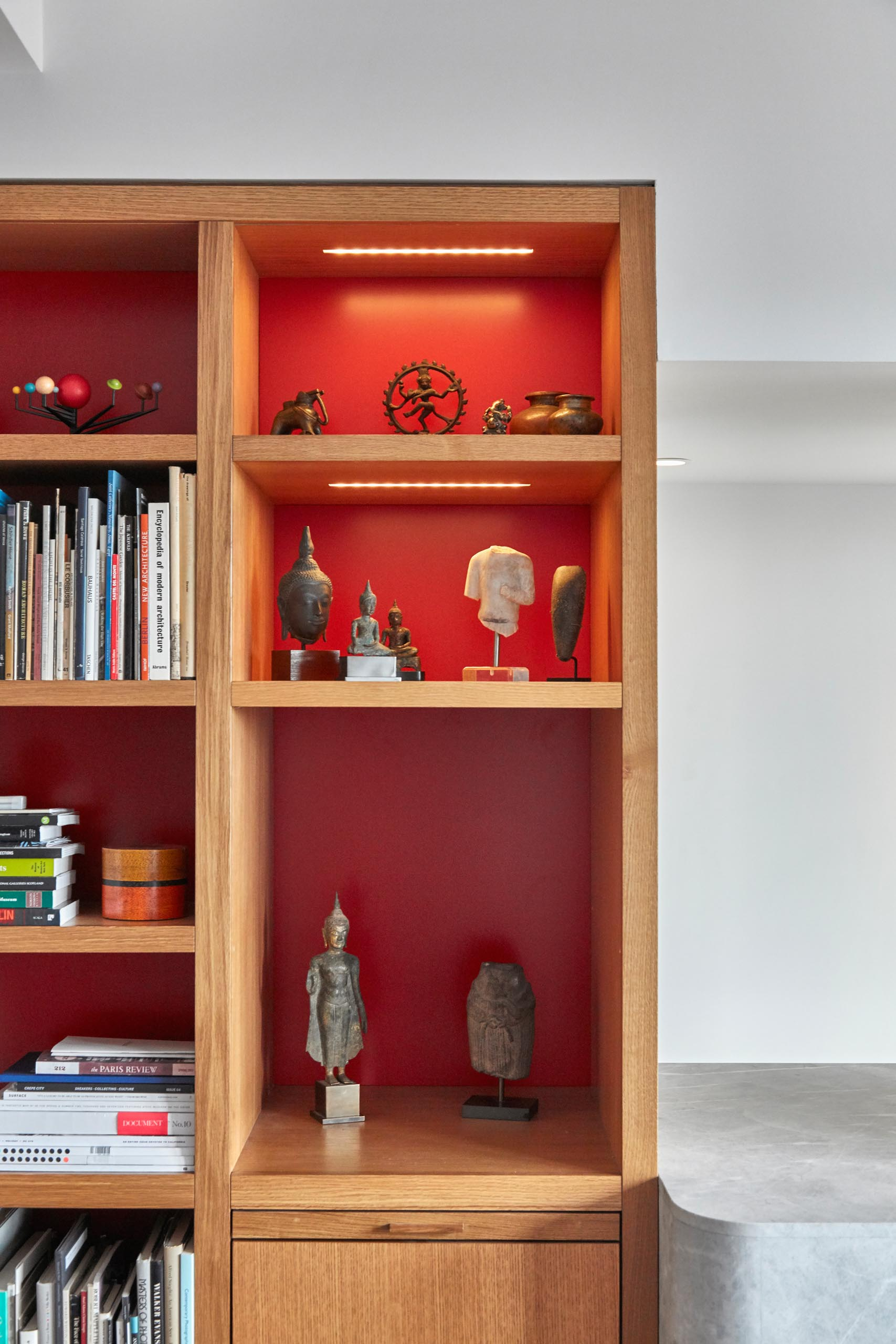Wood shelves with a red backing and LED lighting.