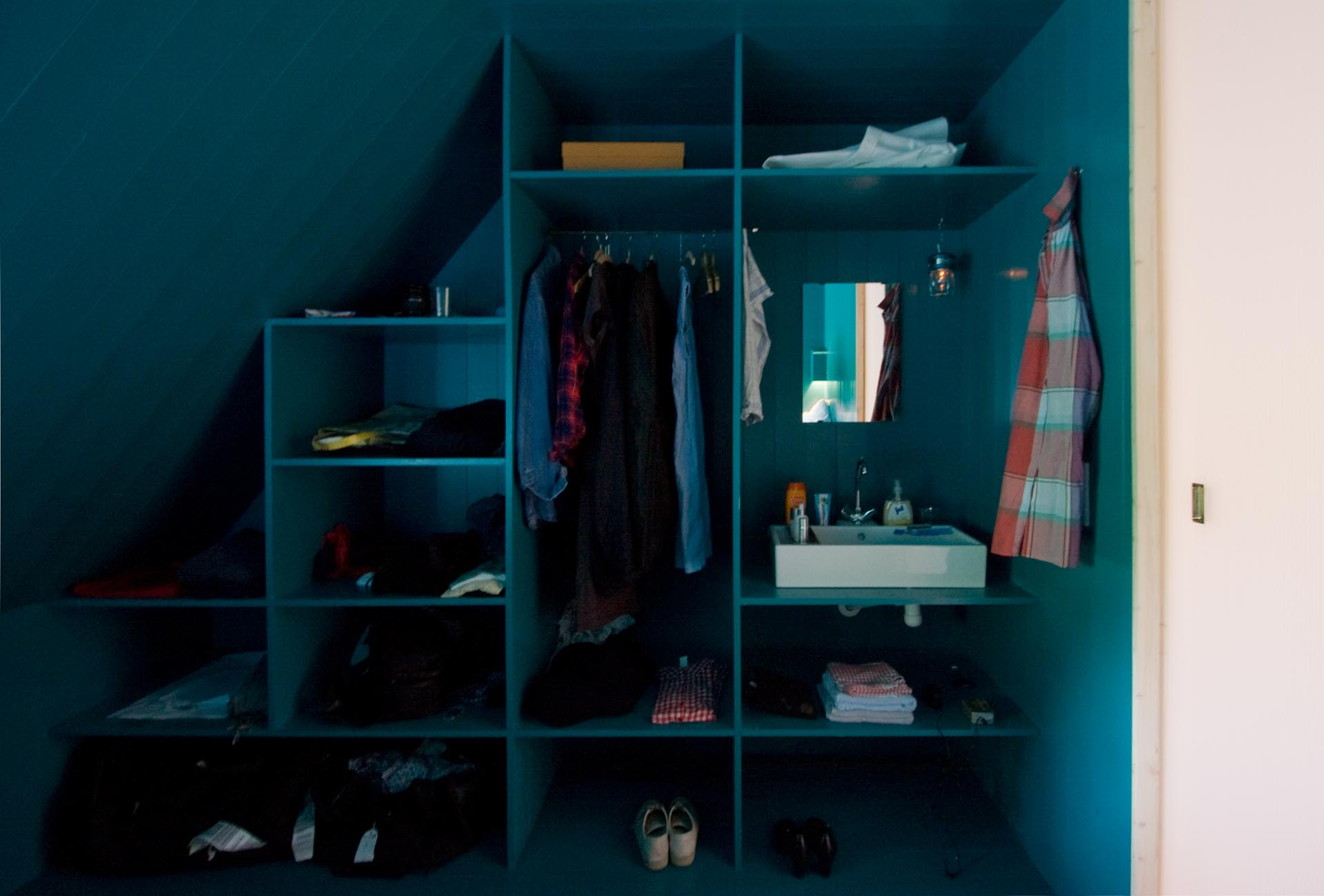 A modern turquoise blue closet that includes a vanity.