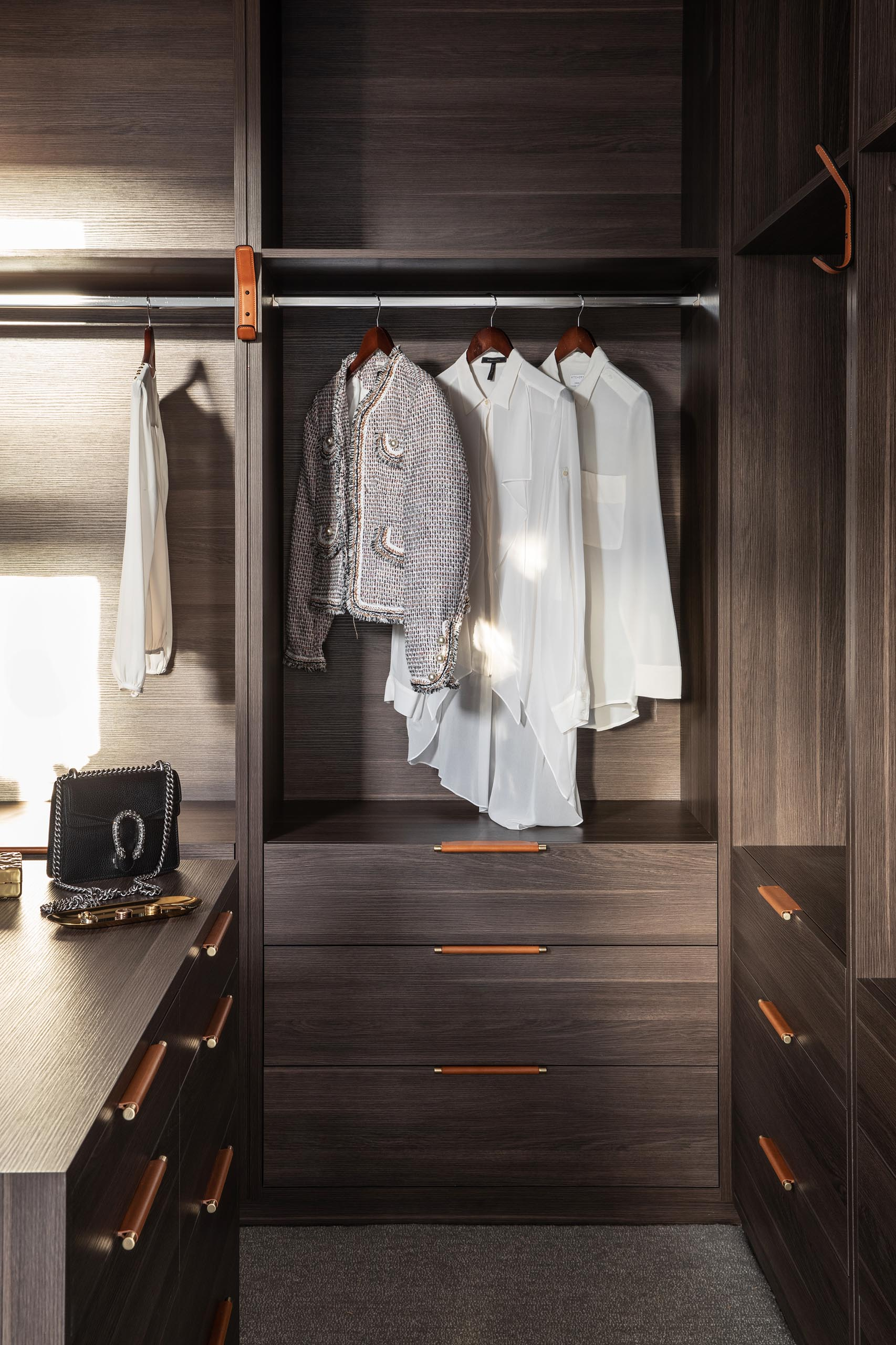 A modern walk-in closet showcases dark wood cabinetry with metal and leather drawer pulls.