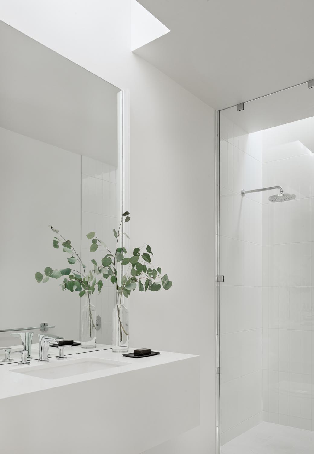 A modern white bathroom with a skylight that highlights the vanity, and a floor-to-ceiling glass screen separates the shower.