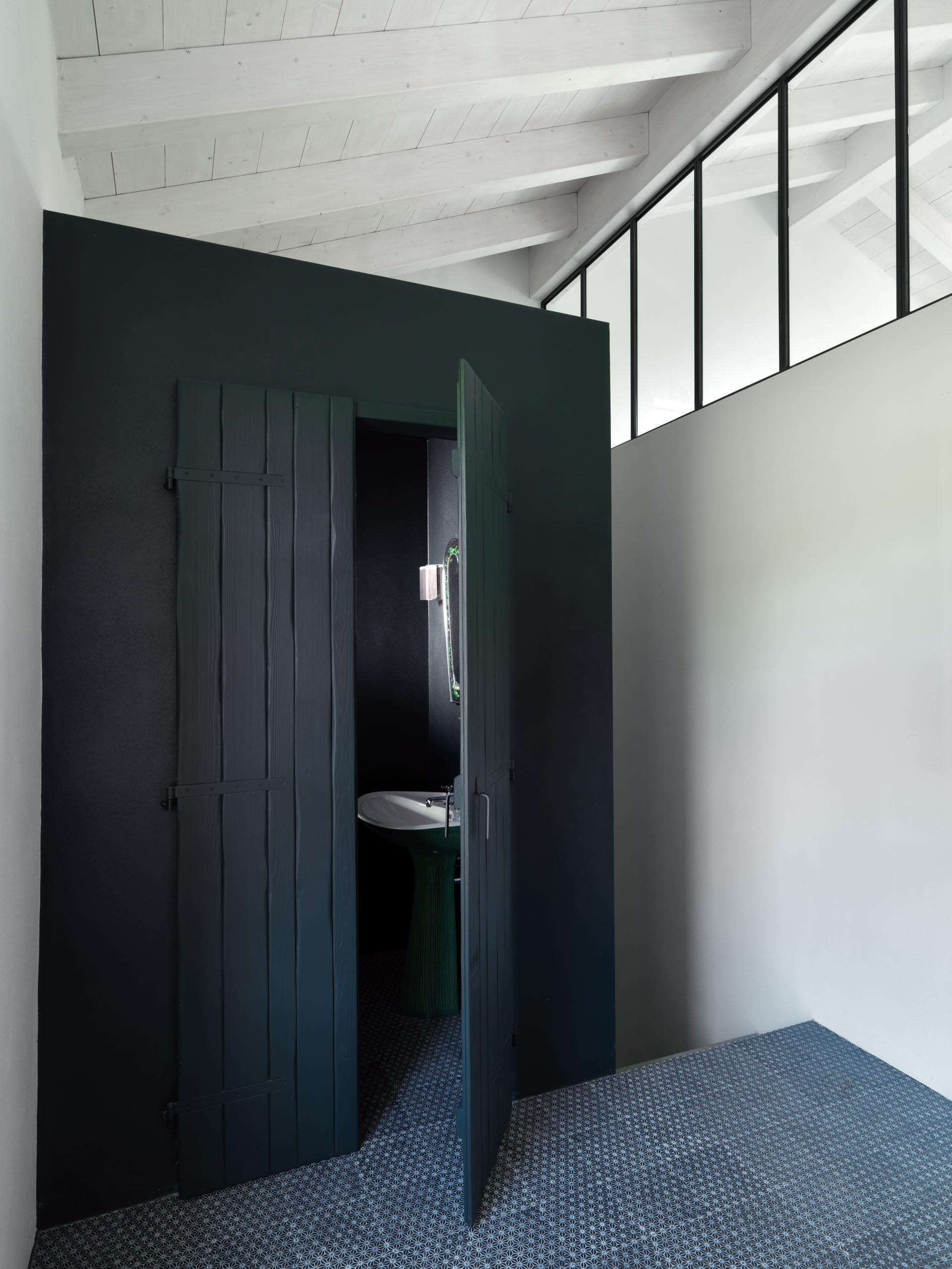 A powder room with matte black painted wood doors.